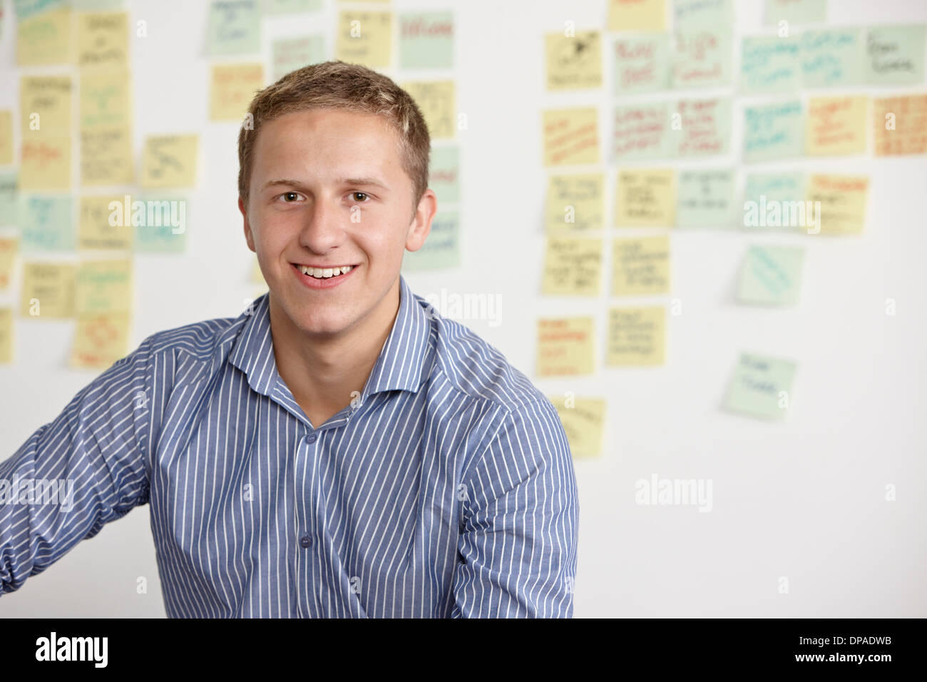 Portrait of young man with adhesive notes in background - Stock Image