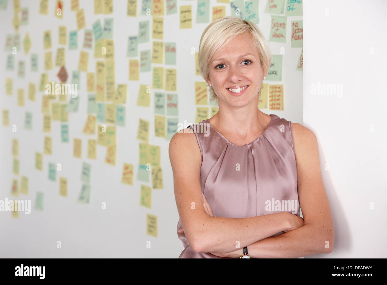 Portrait of mid adult woman with adhesive notes in background - Stock Image