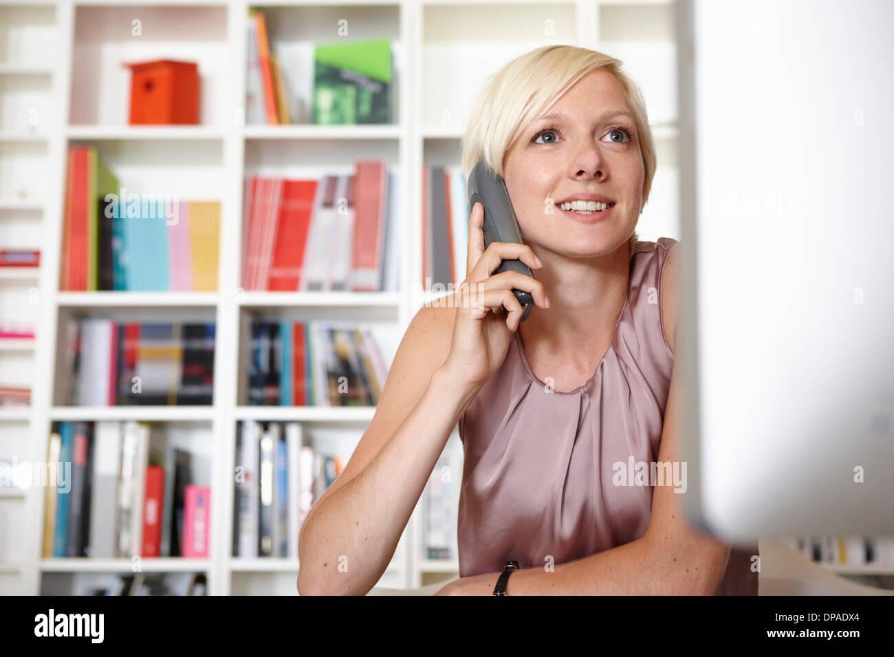 Mid adult woman on landline phone - Stock Image