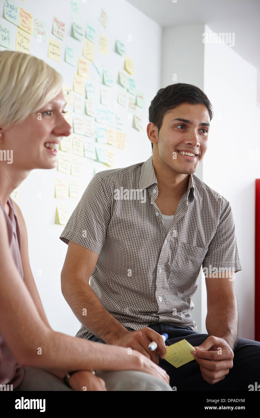 Colleagues listening, man holding adhesive note - Stock Image