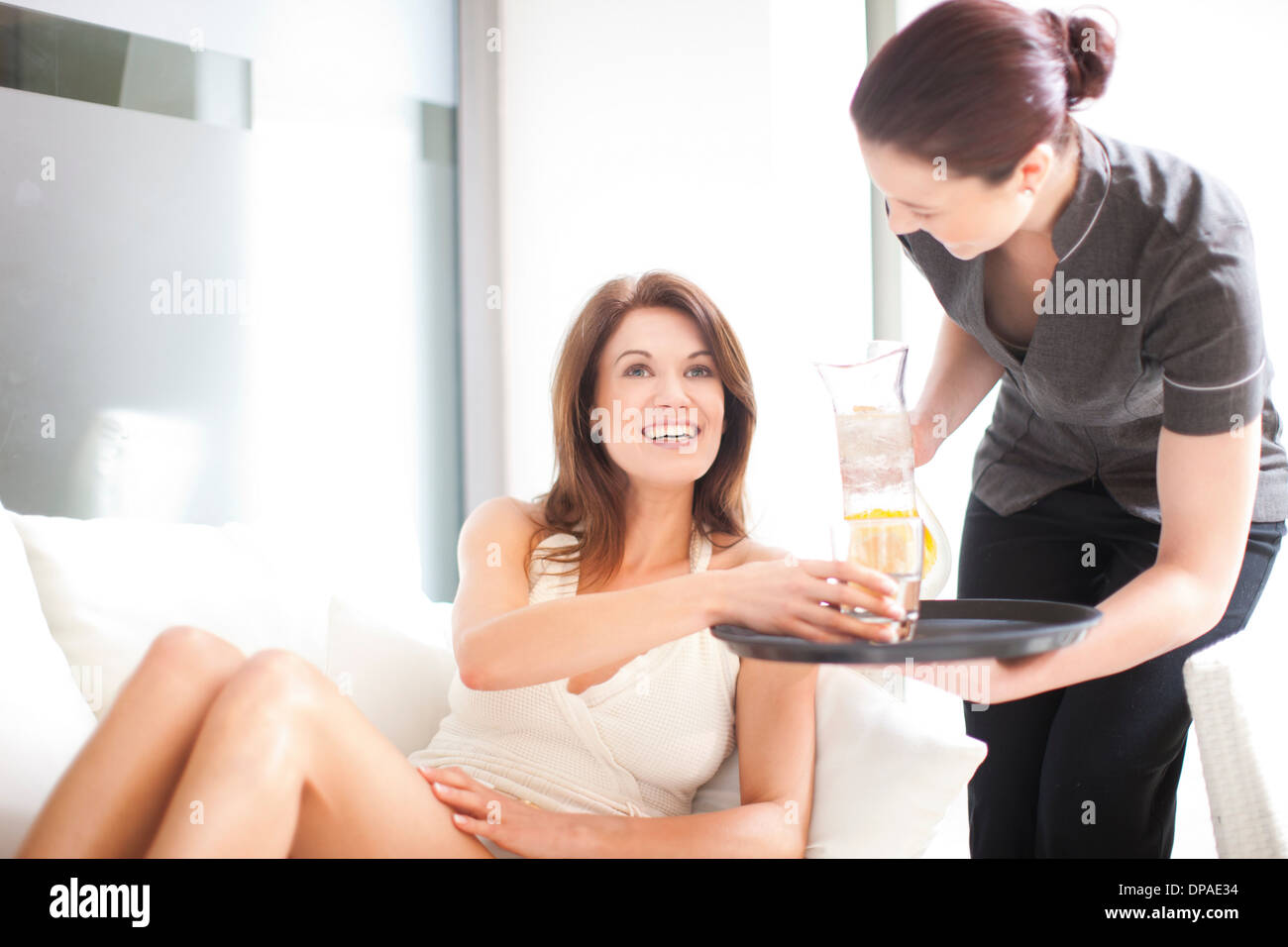 Service worker pouring refreshment for woman poolside - Stock Image