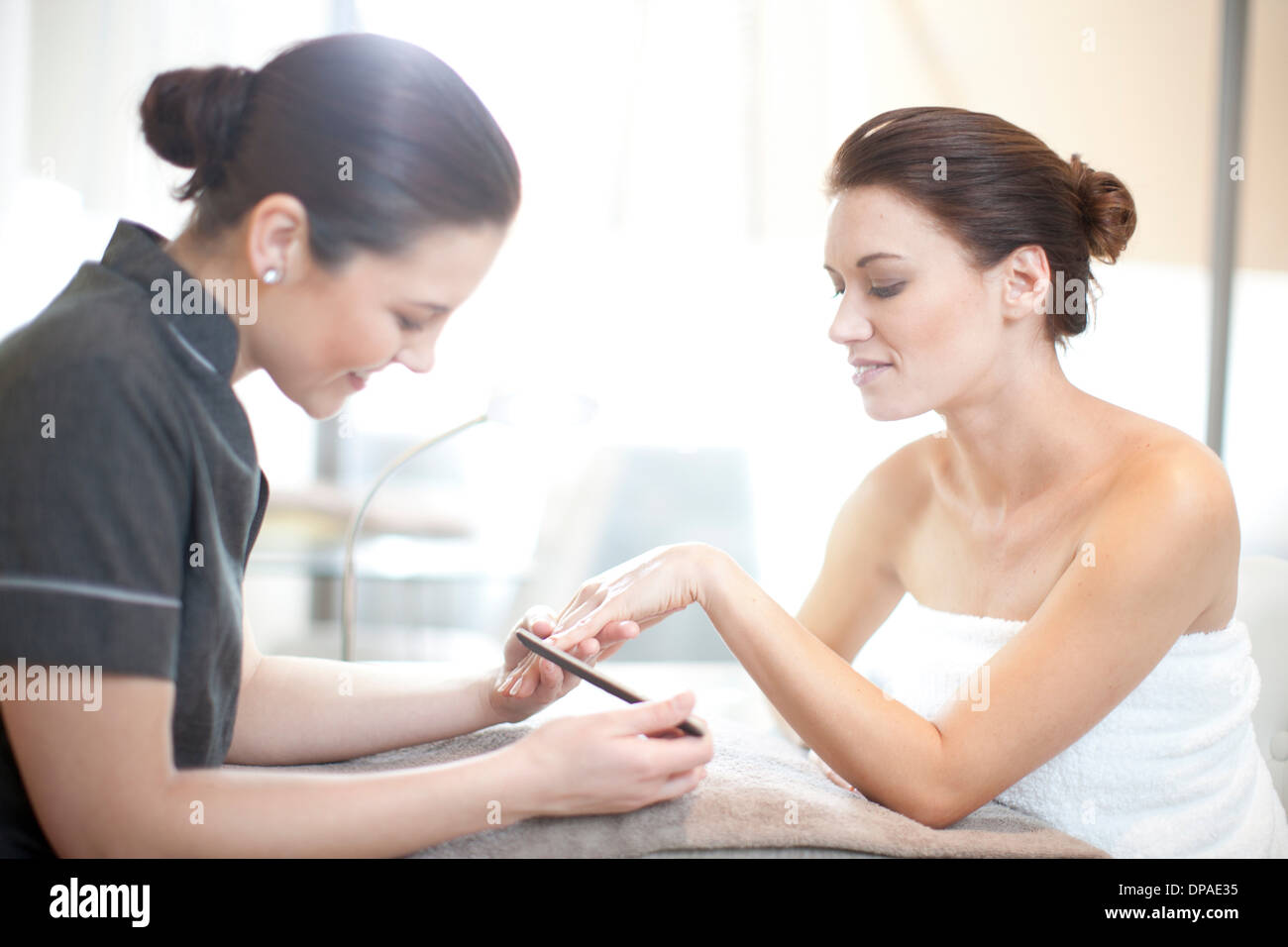 Woman having her nails done in spa treatment room - Stock Image