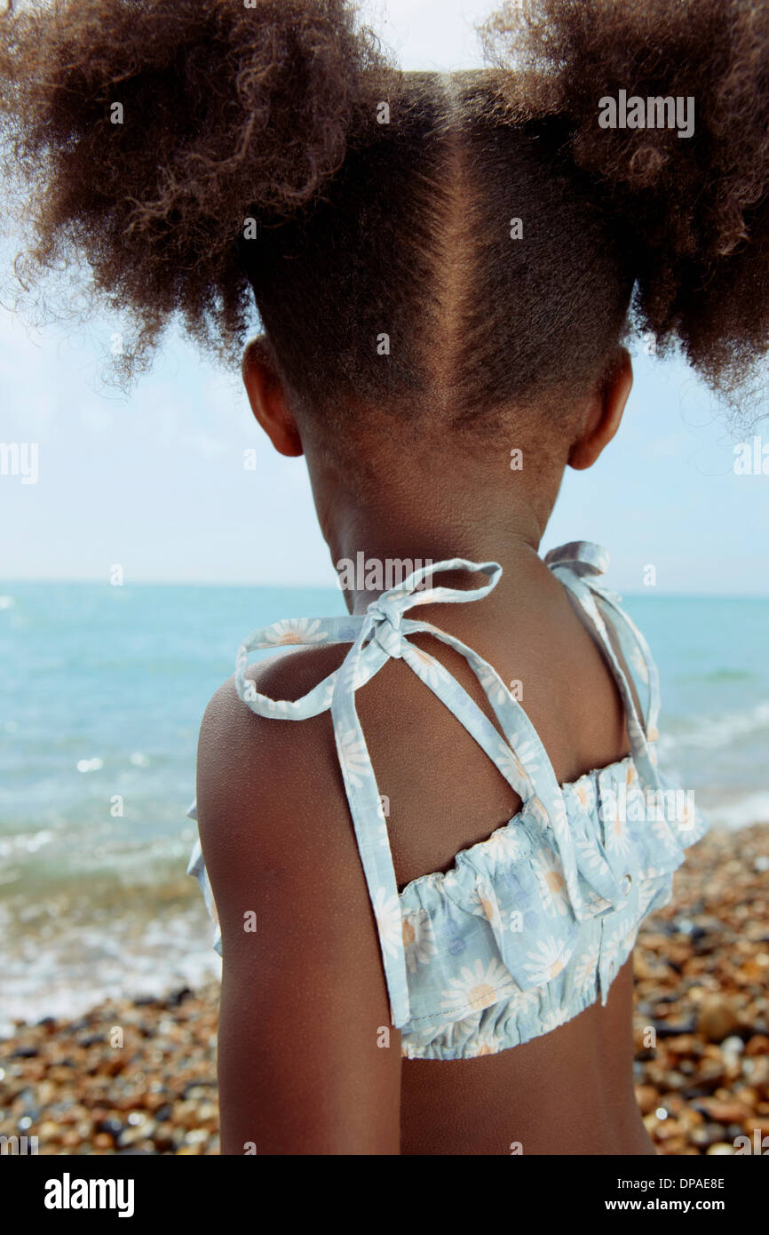 Backview of child looking at ocean - Stock Image