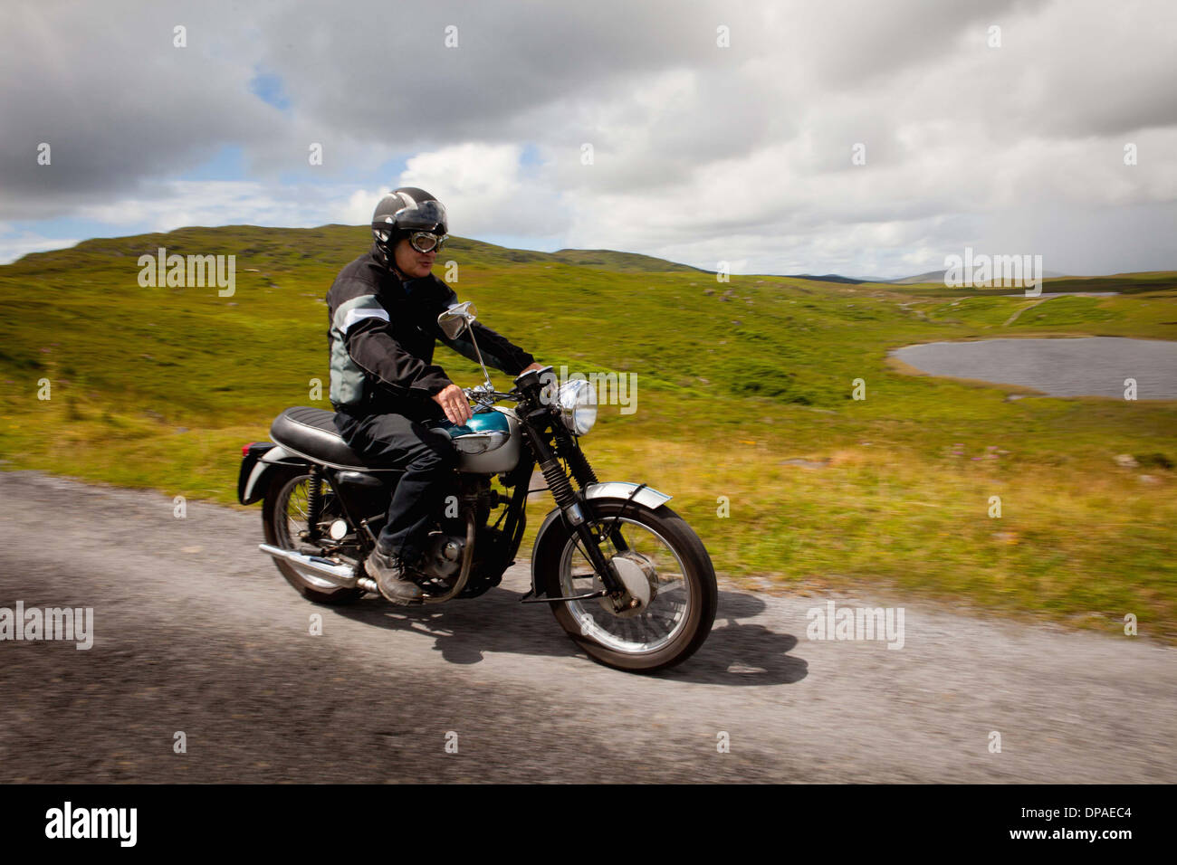 Senior male on motorbike on rural road - Stock Image