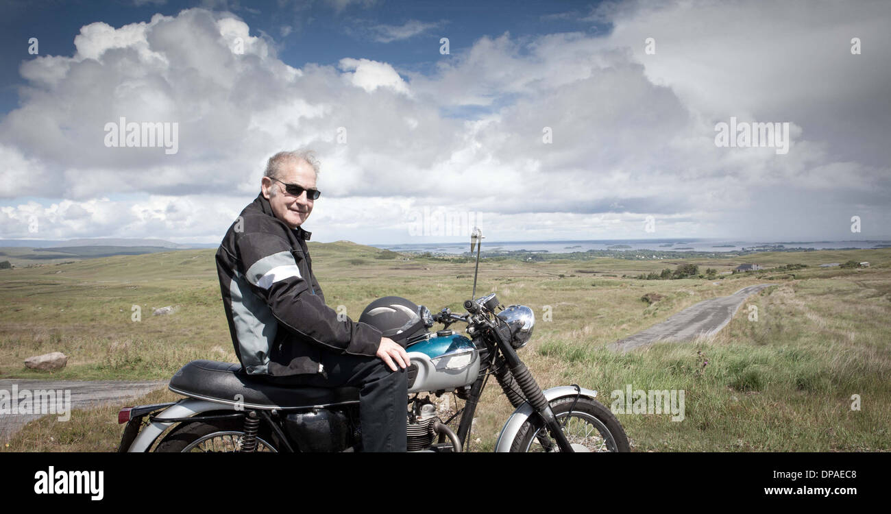 Senior male motorcyclist taking a break - Stock Image