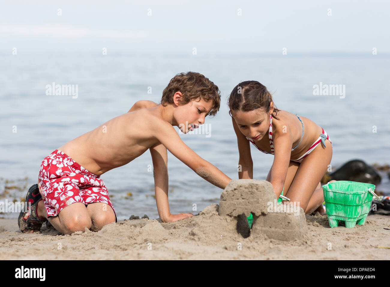 Brother and sister on beach building sandcastle - Stock Image