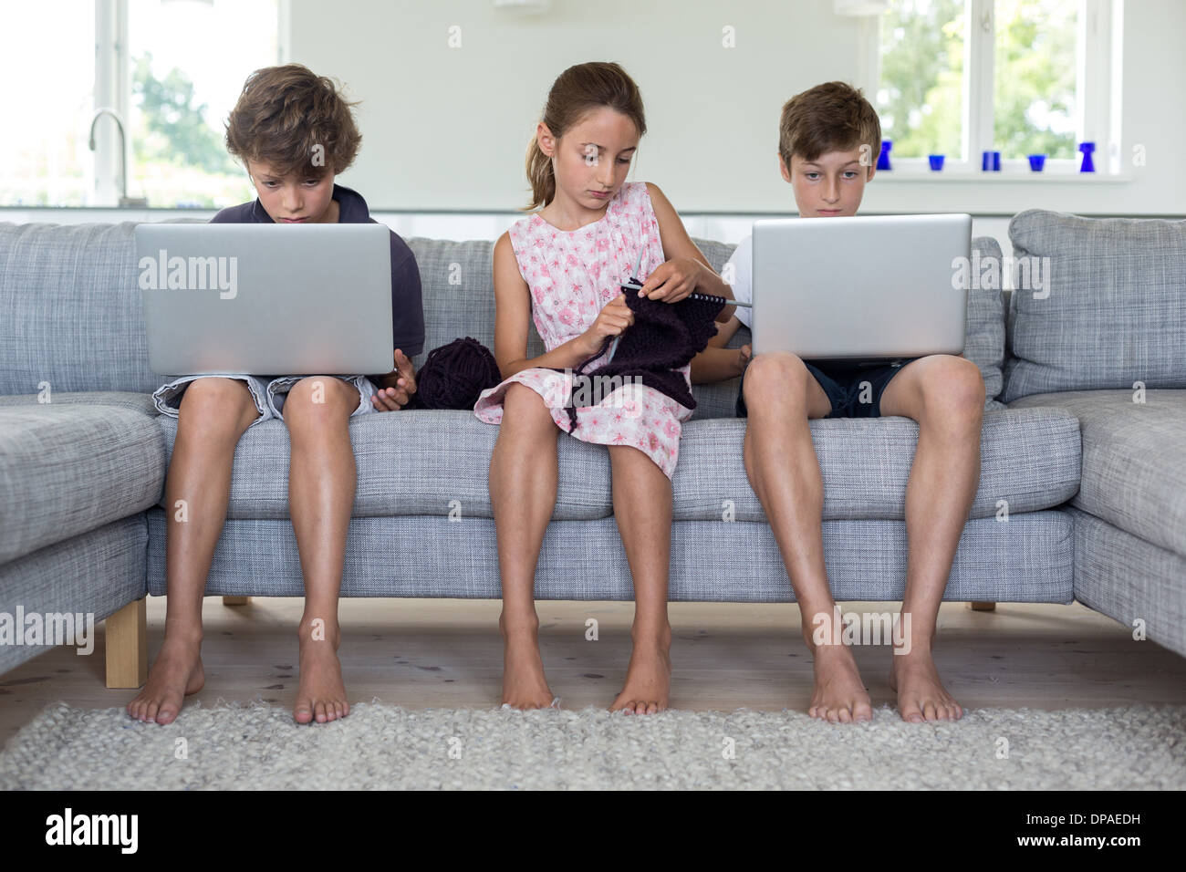 Brothers and sister on sofa with computers and knitting - Stock Image