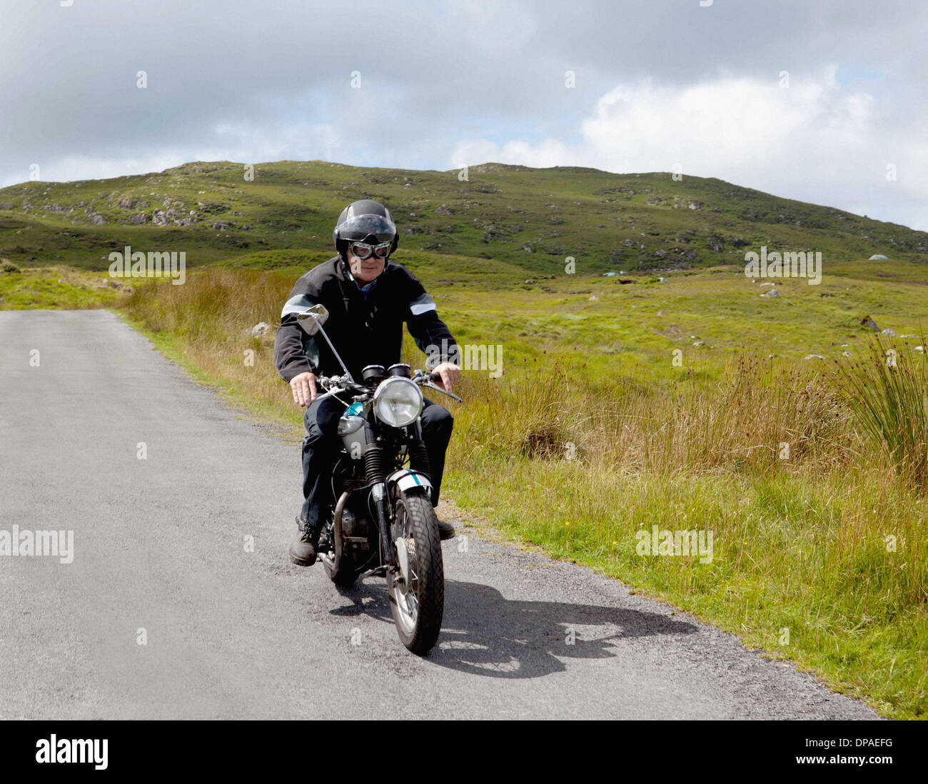 Senior male motorcyclist riding on rural road - Stock Image
