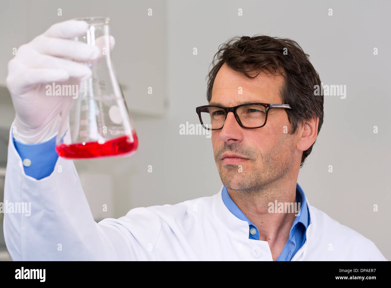 Male scientist examining ph-reaction of liquid in flask - Stock Image