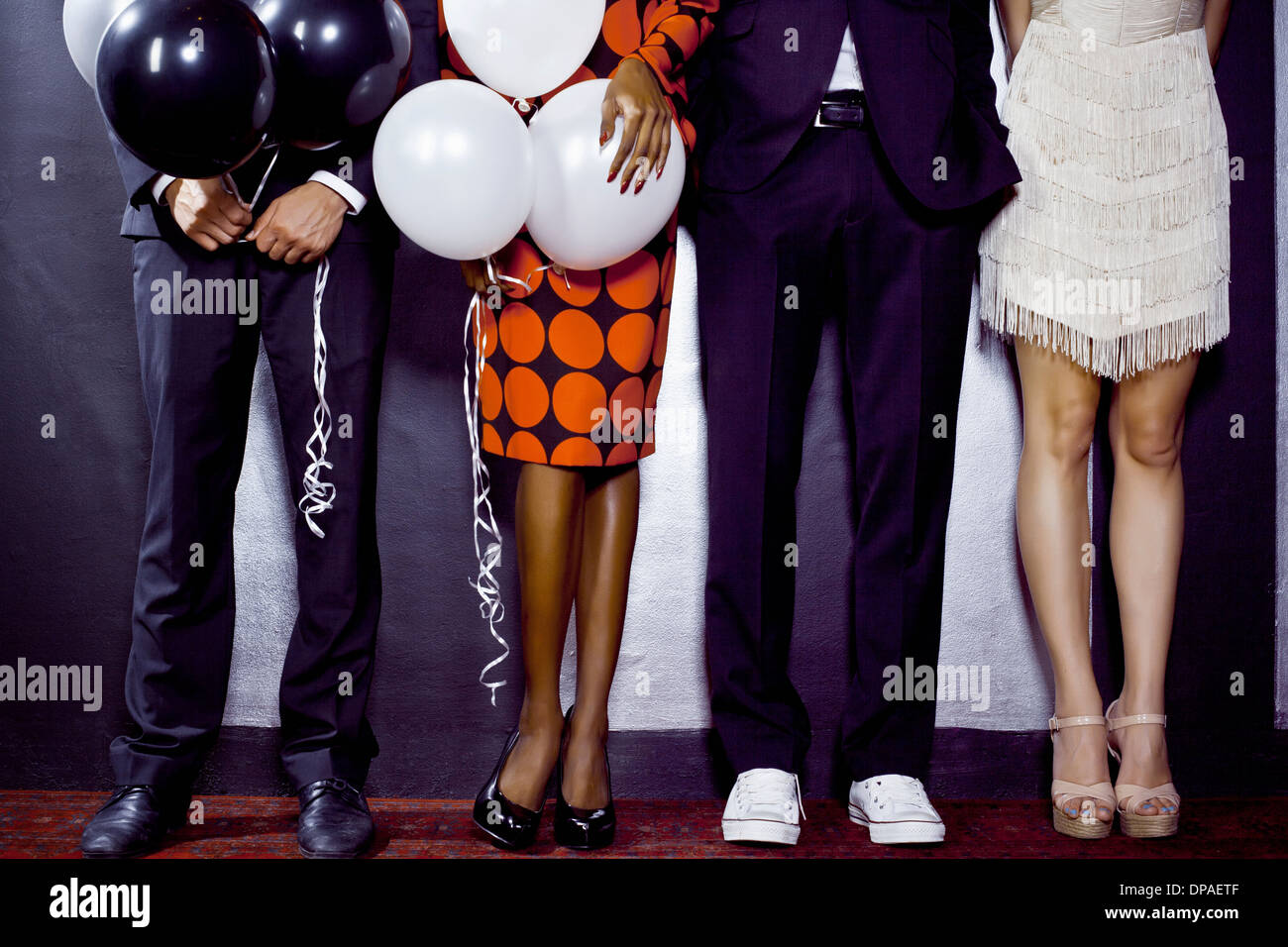 Waist down shot of group of friends with balloons - Stock Image