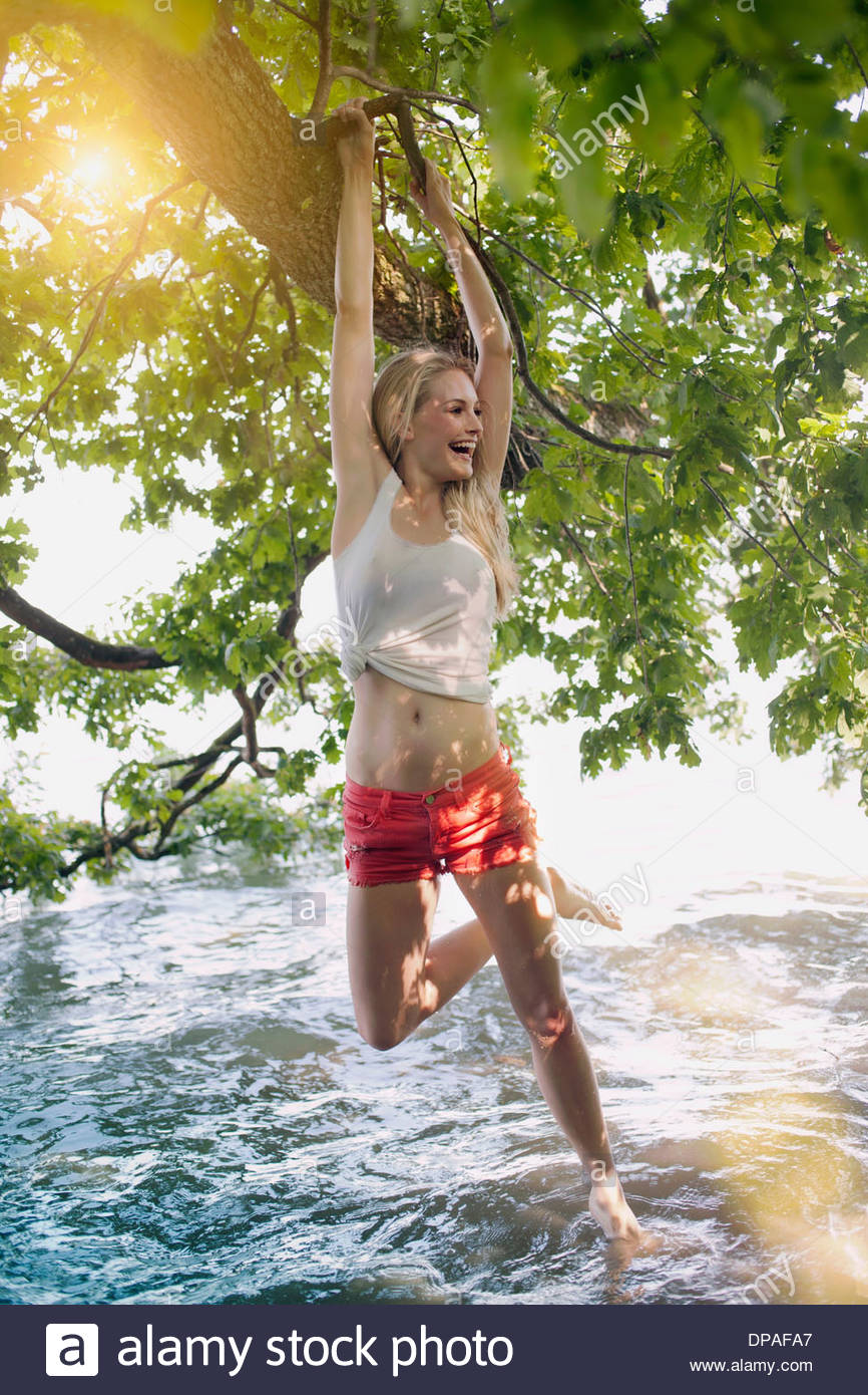 Young woman hanging from tree branch into lake - Stock Image