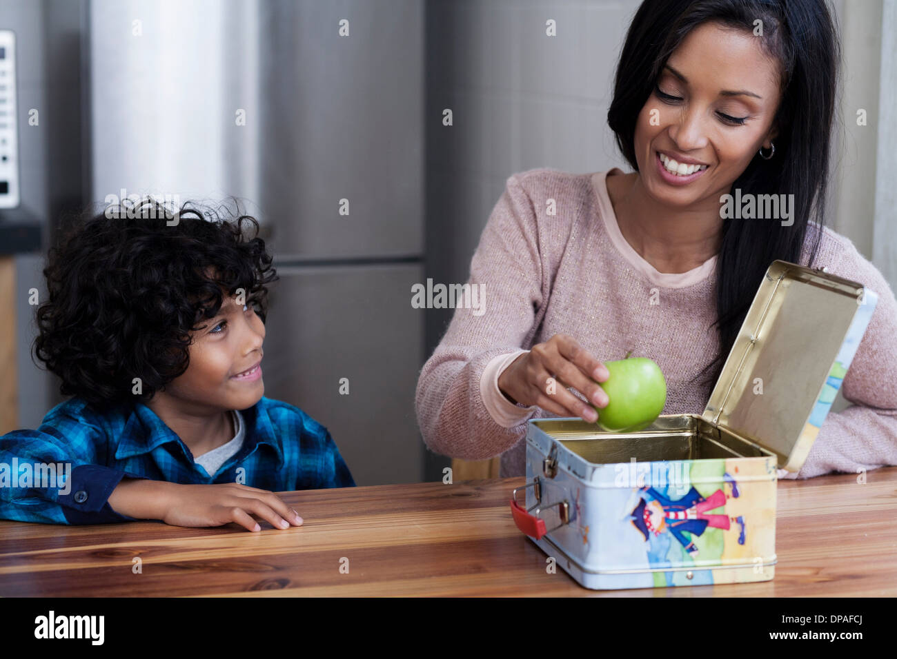 Mother and son packing lunch box - Stock Image