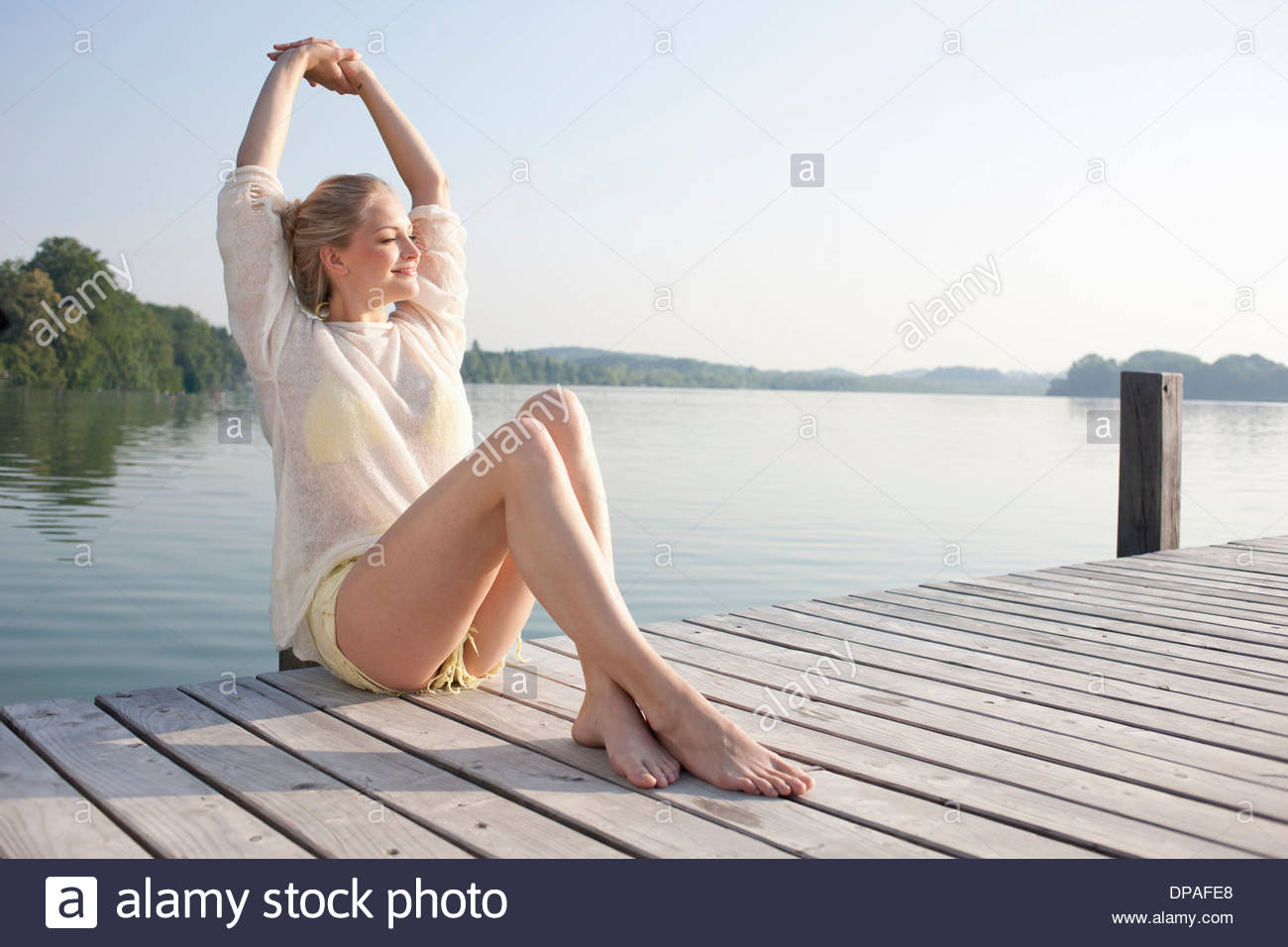 Young woman relaxing on lake pier Stock Photo