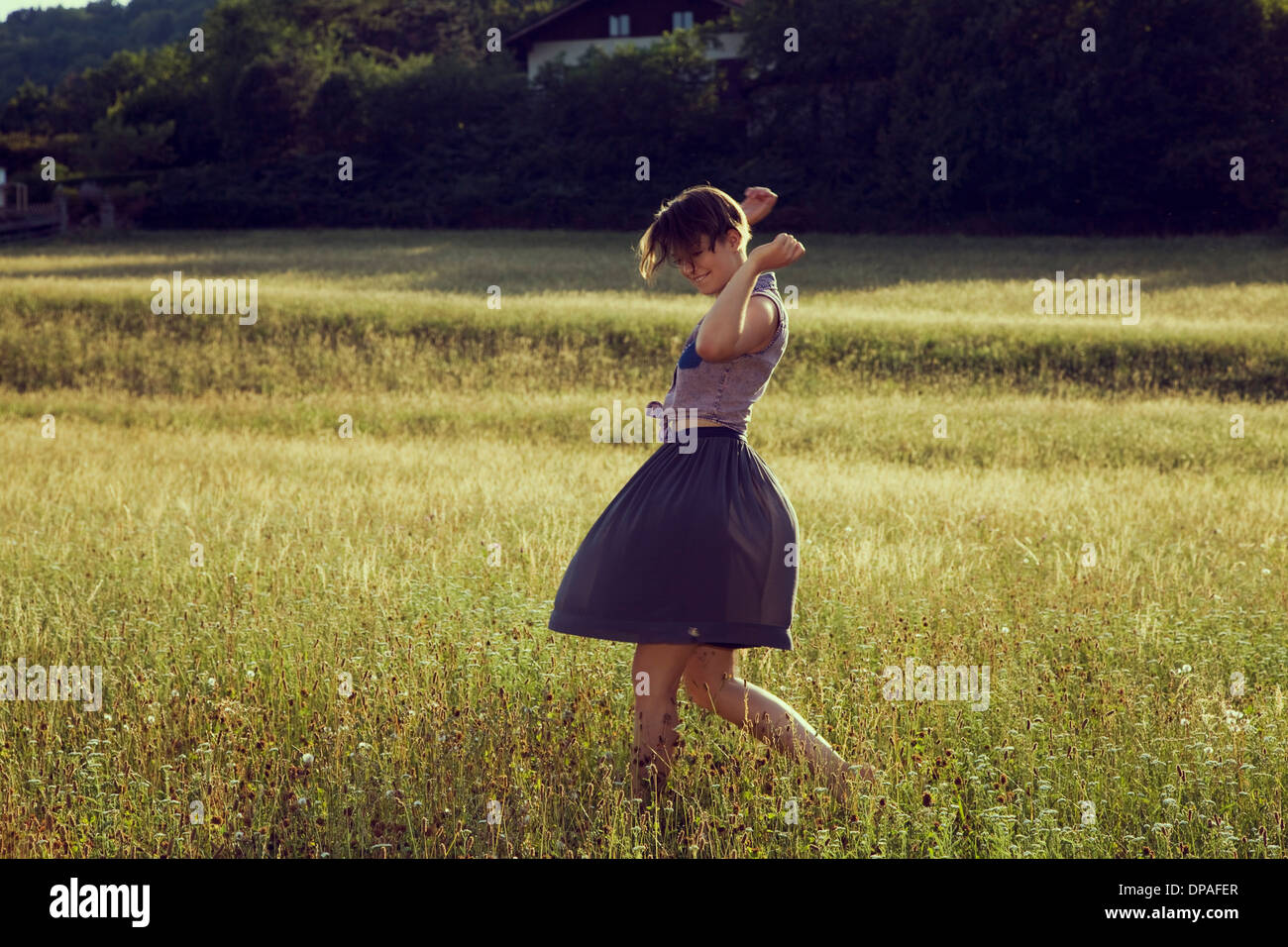 Young woman walking through meadow - Stock Image