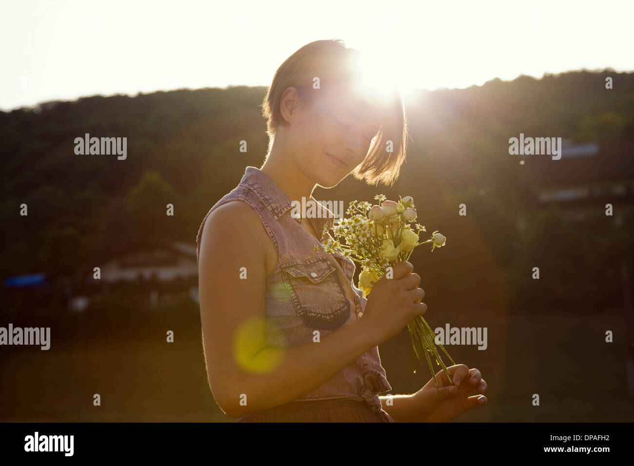 Young woman in meadow holding bunch of wild flowers Stock Photo