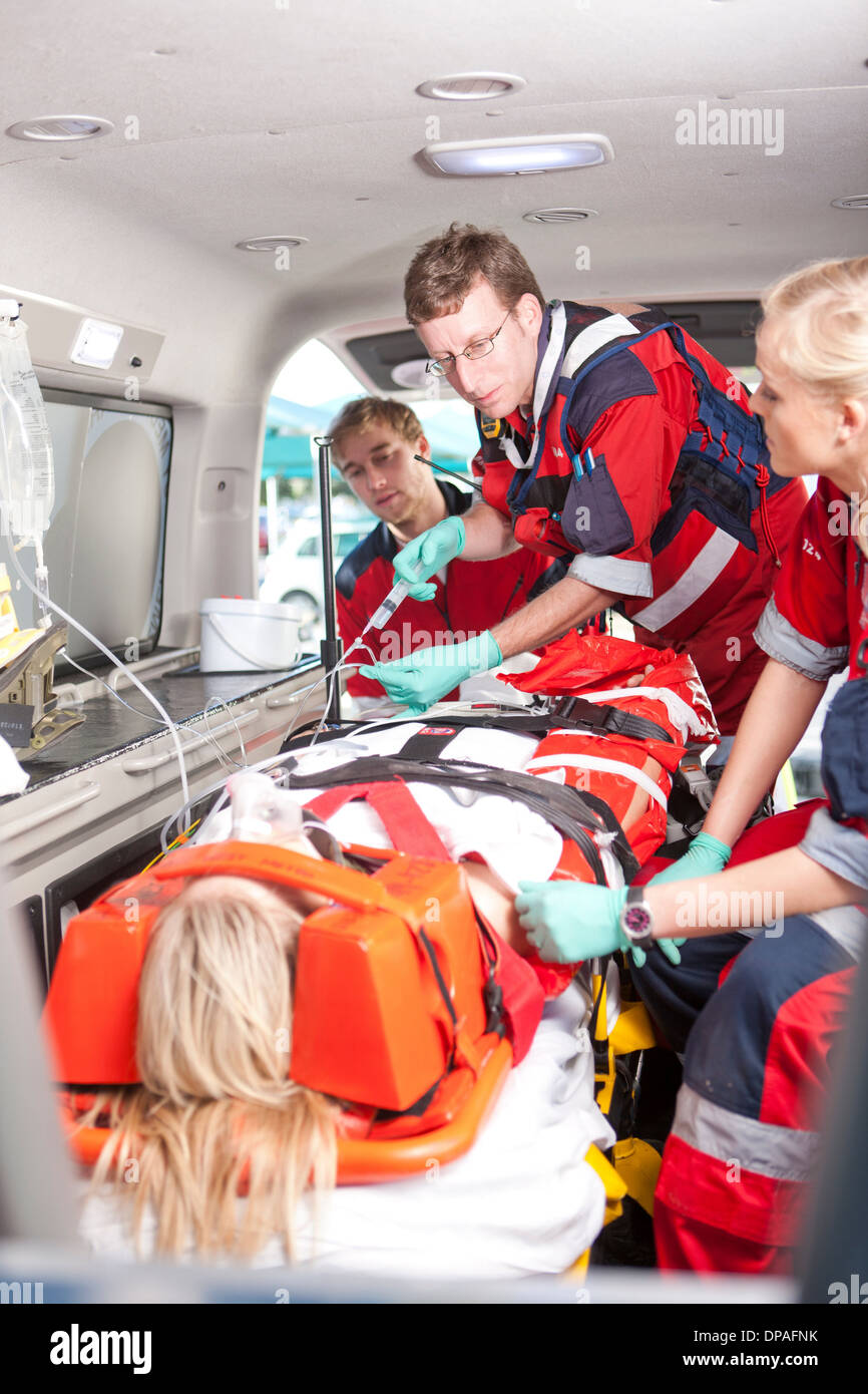 Paramedics with intravenous drip and patient in ambulance - Stock Image