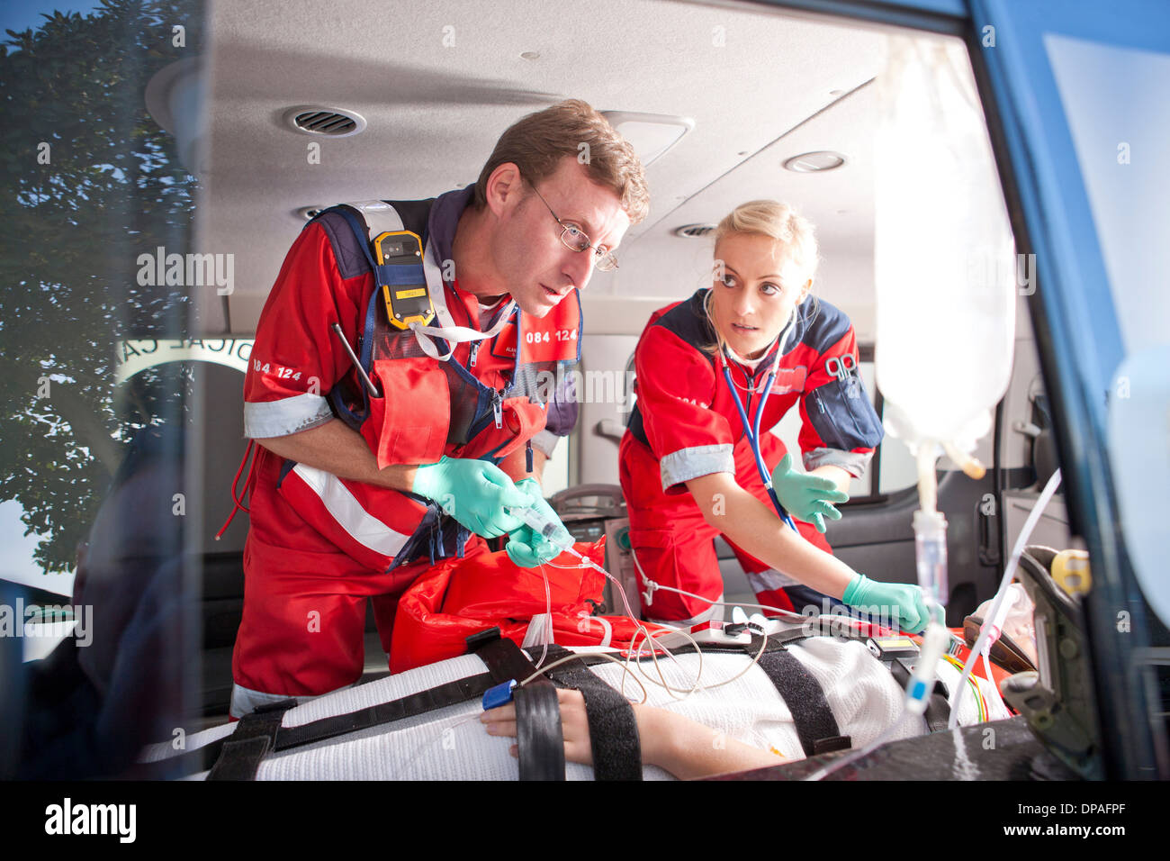Paramedics working on patient in ambulance Stock Photo