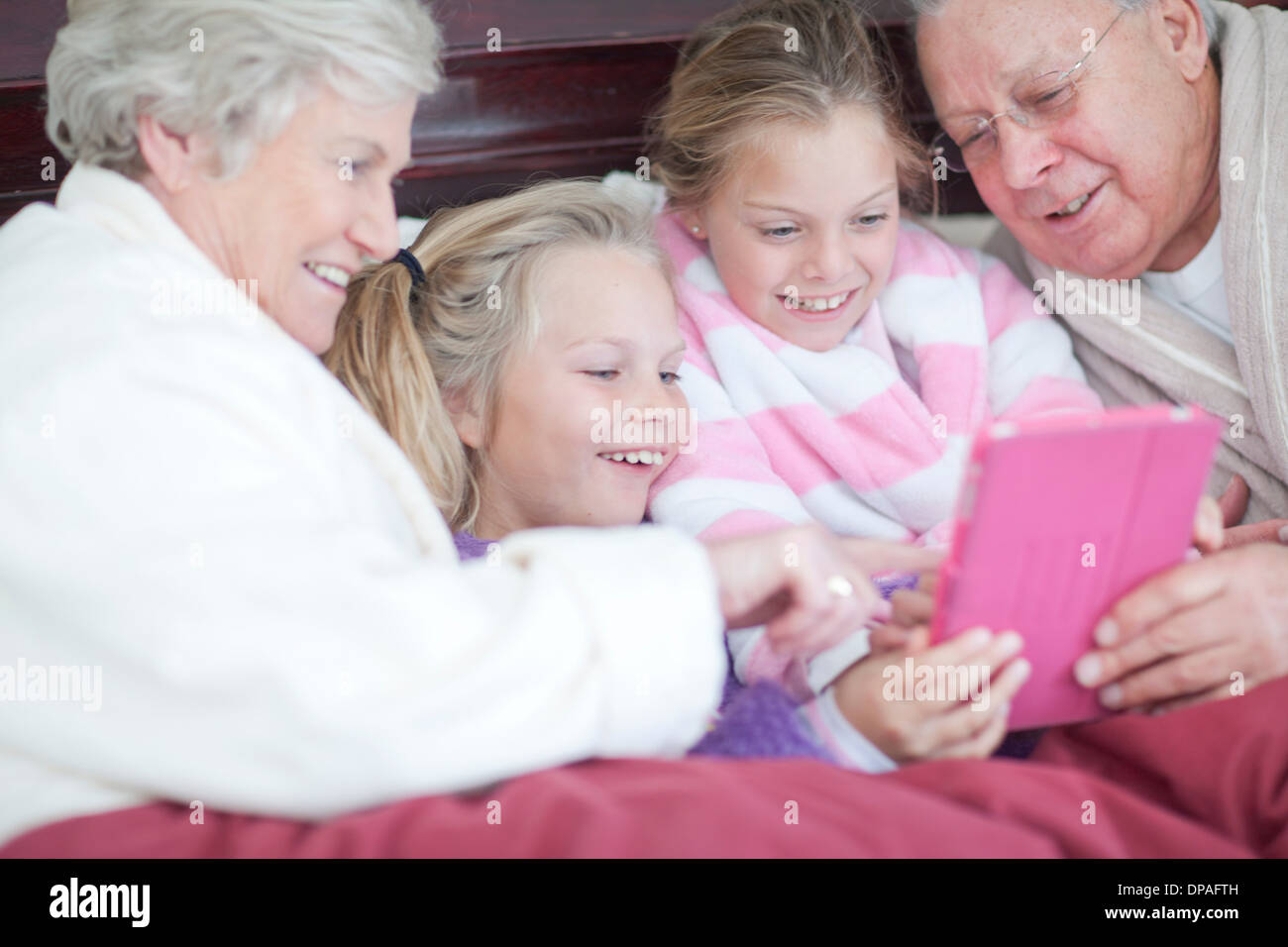 Grandparents and grandchildren playing digital game in bed - Stock Image