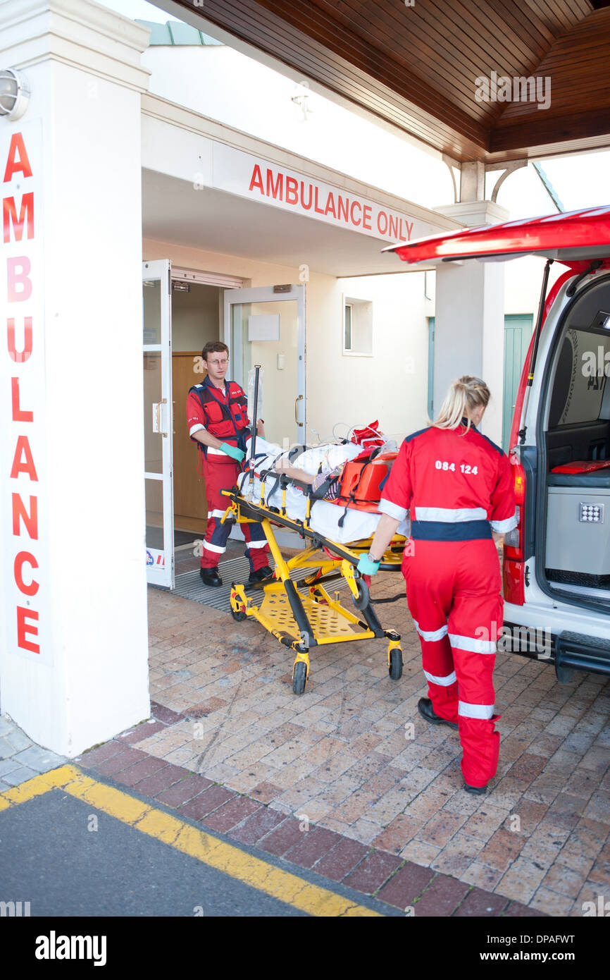 Paramedics moving patient through hospital doorway - Stock Image