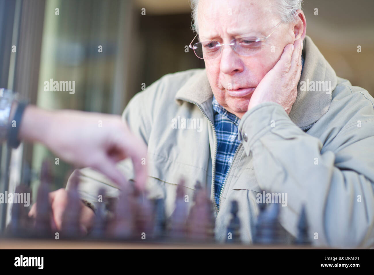 Senior male playing chess with son - Stock Image