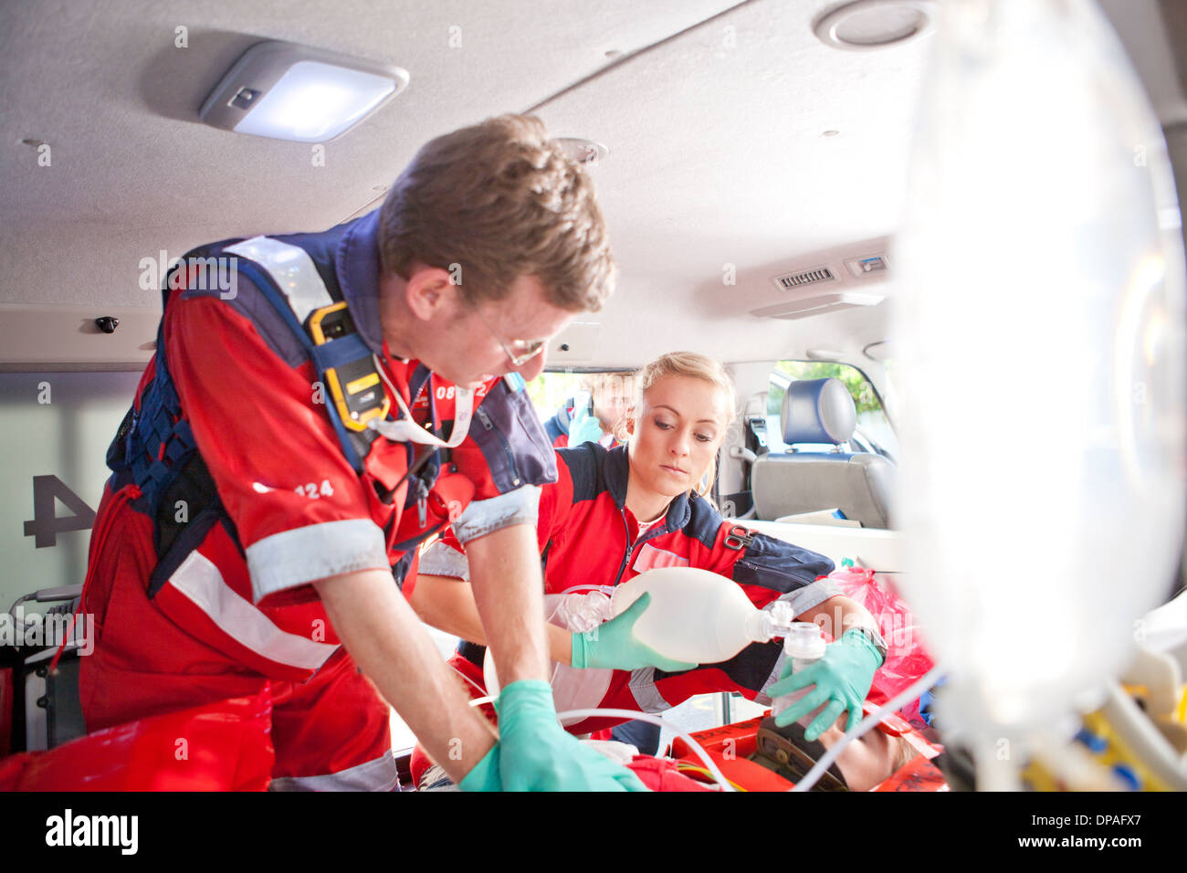 Paramedics giving patient heart massage in ambulance Stock Photo
