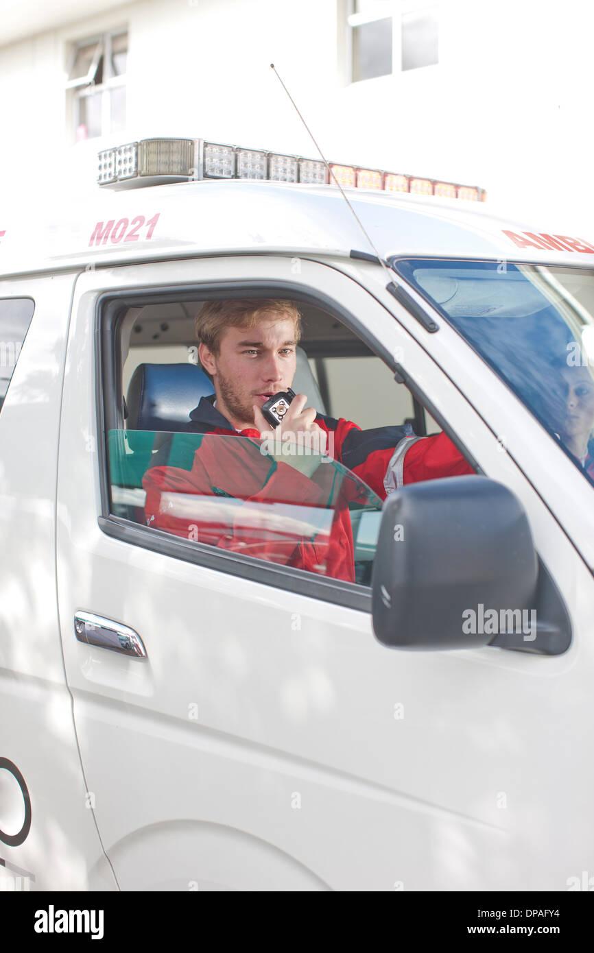 Paramedic in ambulance on walkie-talkie - Stock Image