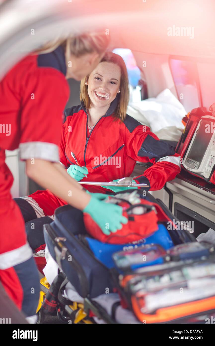 Two female paramedics in ambulance checking equipment - Stock Image