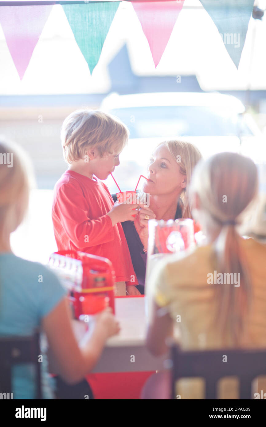 Two young sisters behind stall selling drink to mother - Stock Image