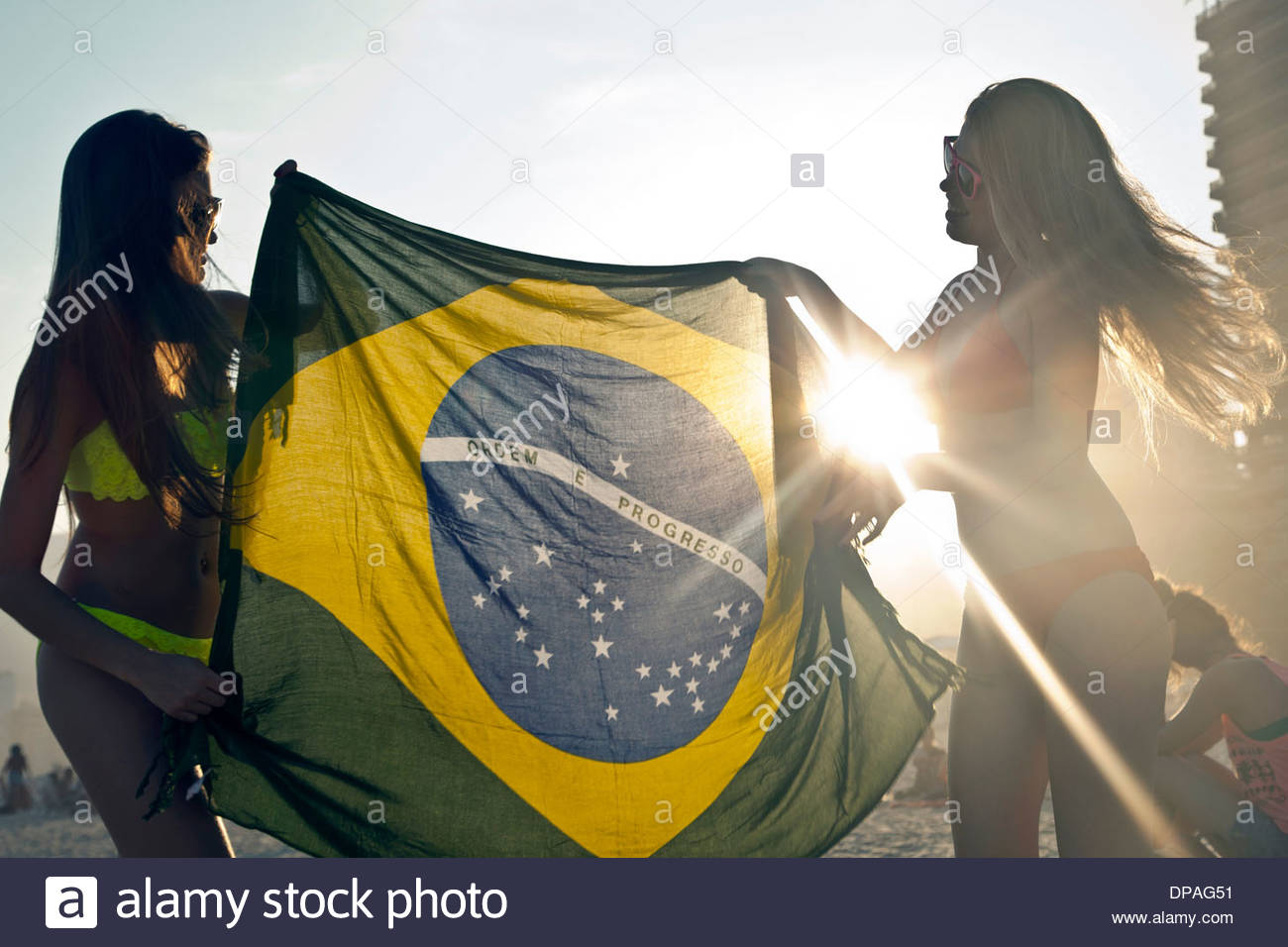 Two young women with Brazilian Flag in sunlight - Stock Image