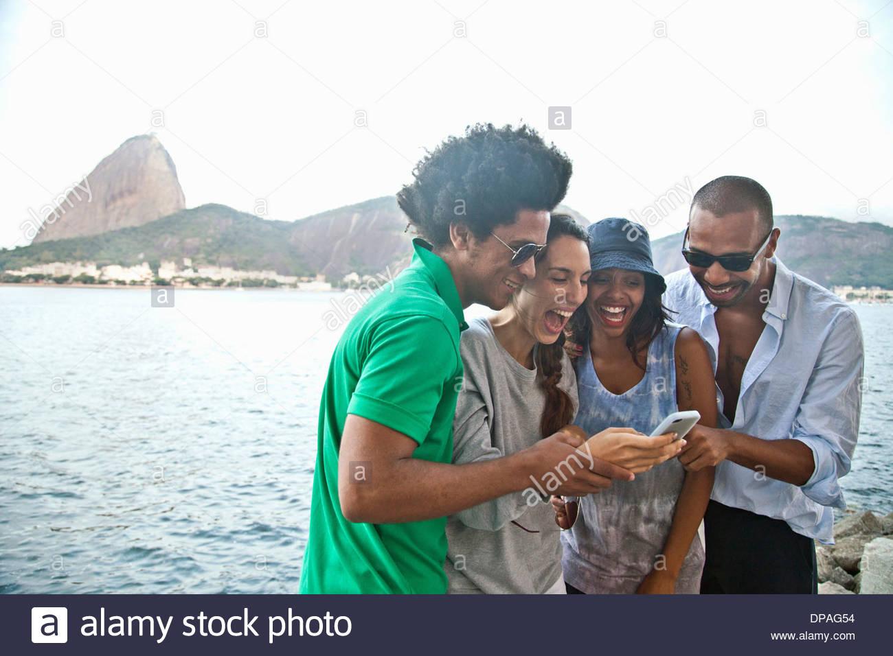 Four friends looking at smartphone, Rio de Janeiro, Brazil - Stock Image