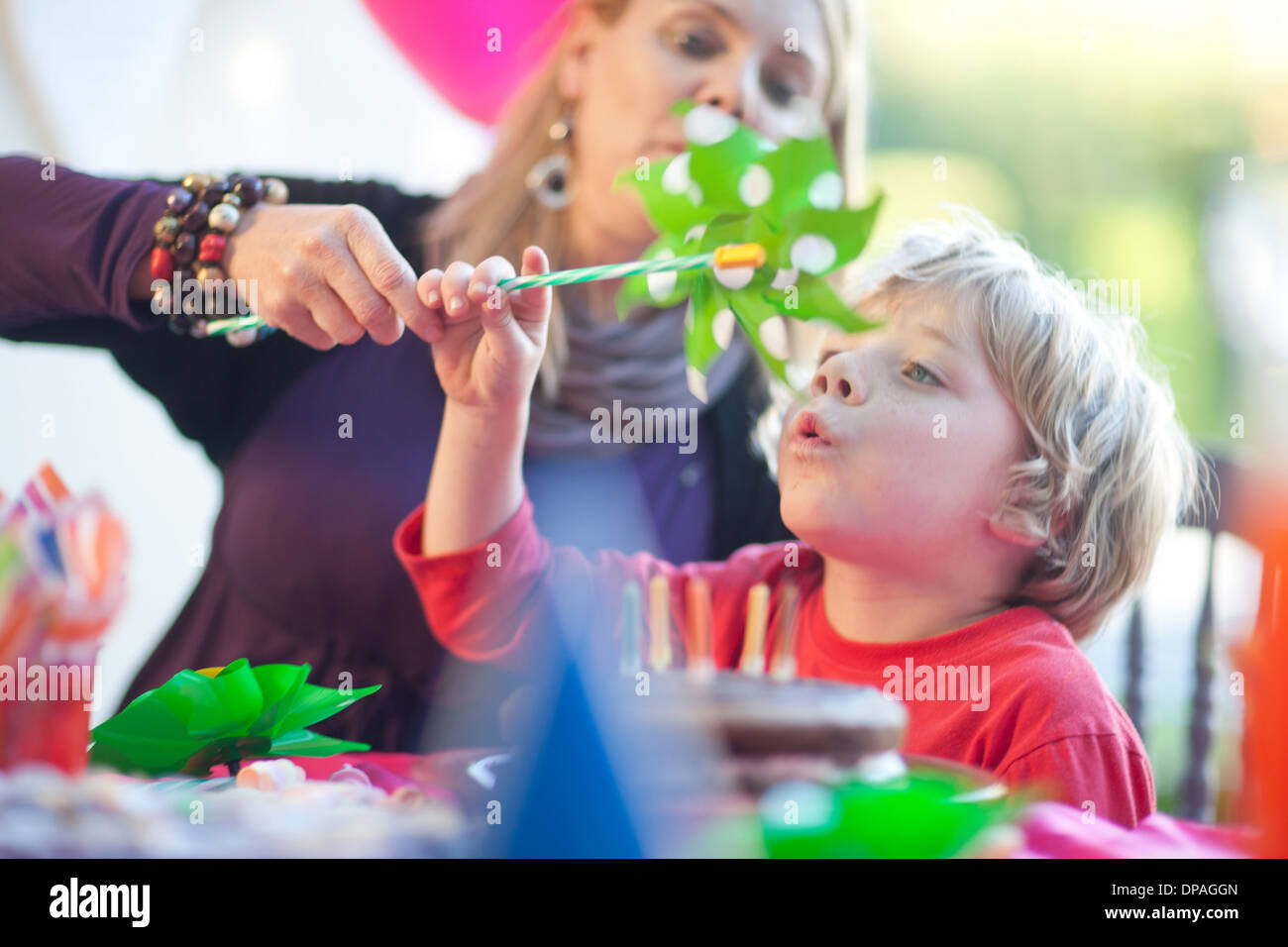 Young boy blowing windmill at birthday party - Stock Image
