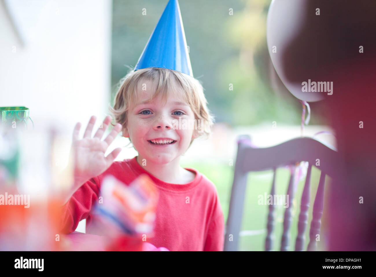 Young boy waving at birthday party - Stock Image