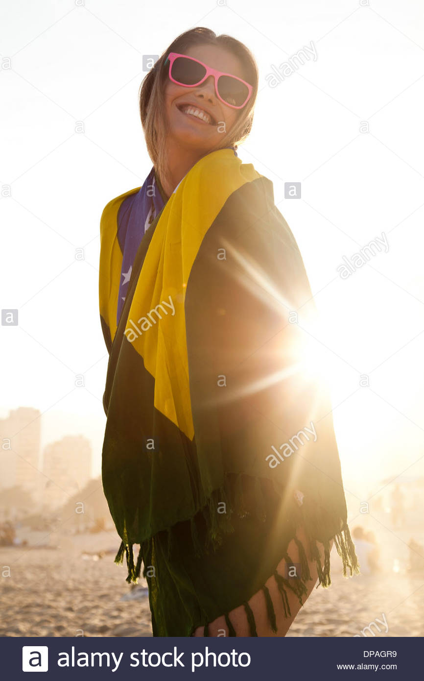 Young woman wrapped in Brazilian Flag in sunlight - Stock Image