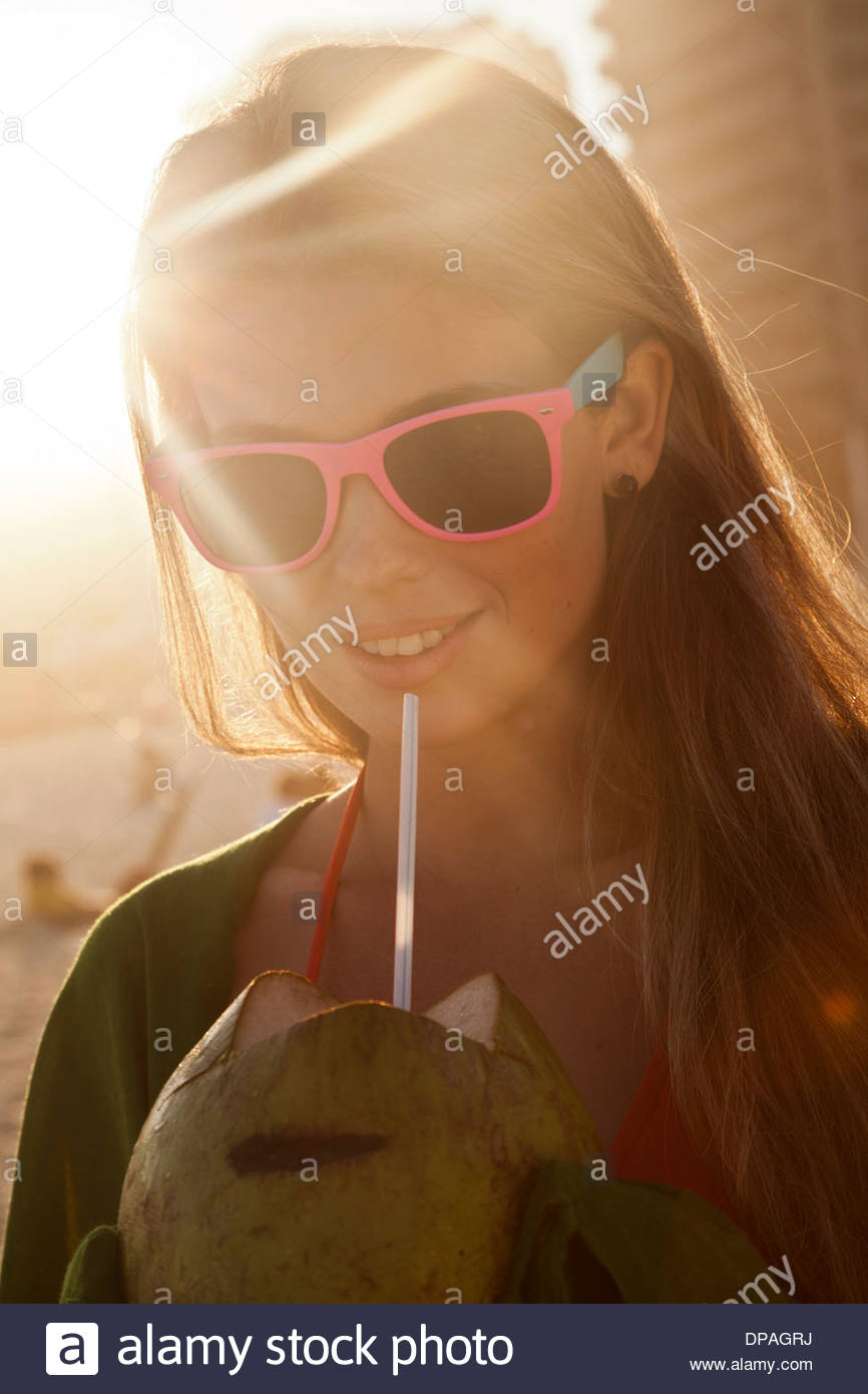 Young woman in sunlight with coconut drink - Stock Image