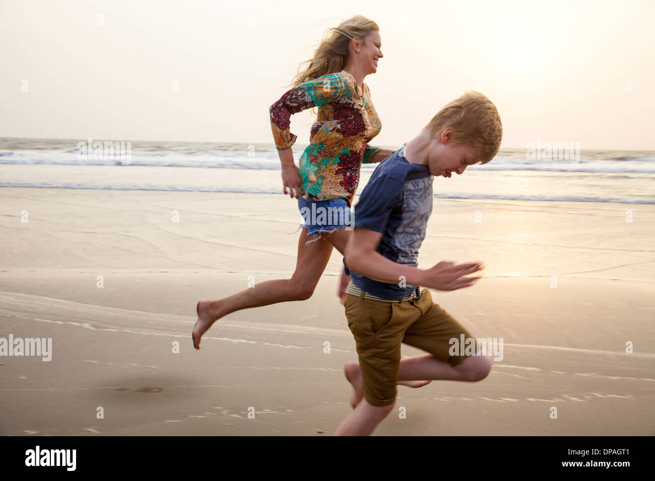 Mother and son running on beach - Stock Image