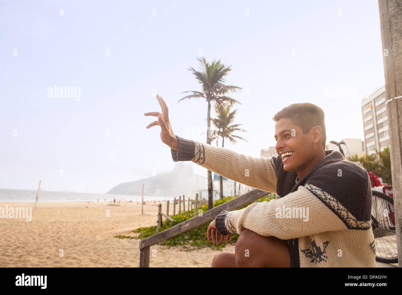 Young man waving, Ipanema Beach, Rio de Janeiro, Brazil - Stock Image