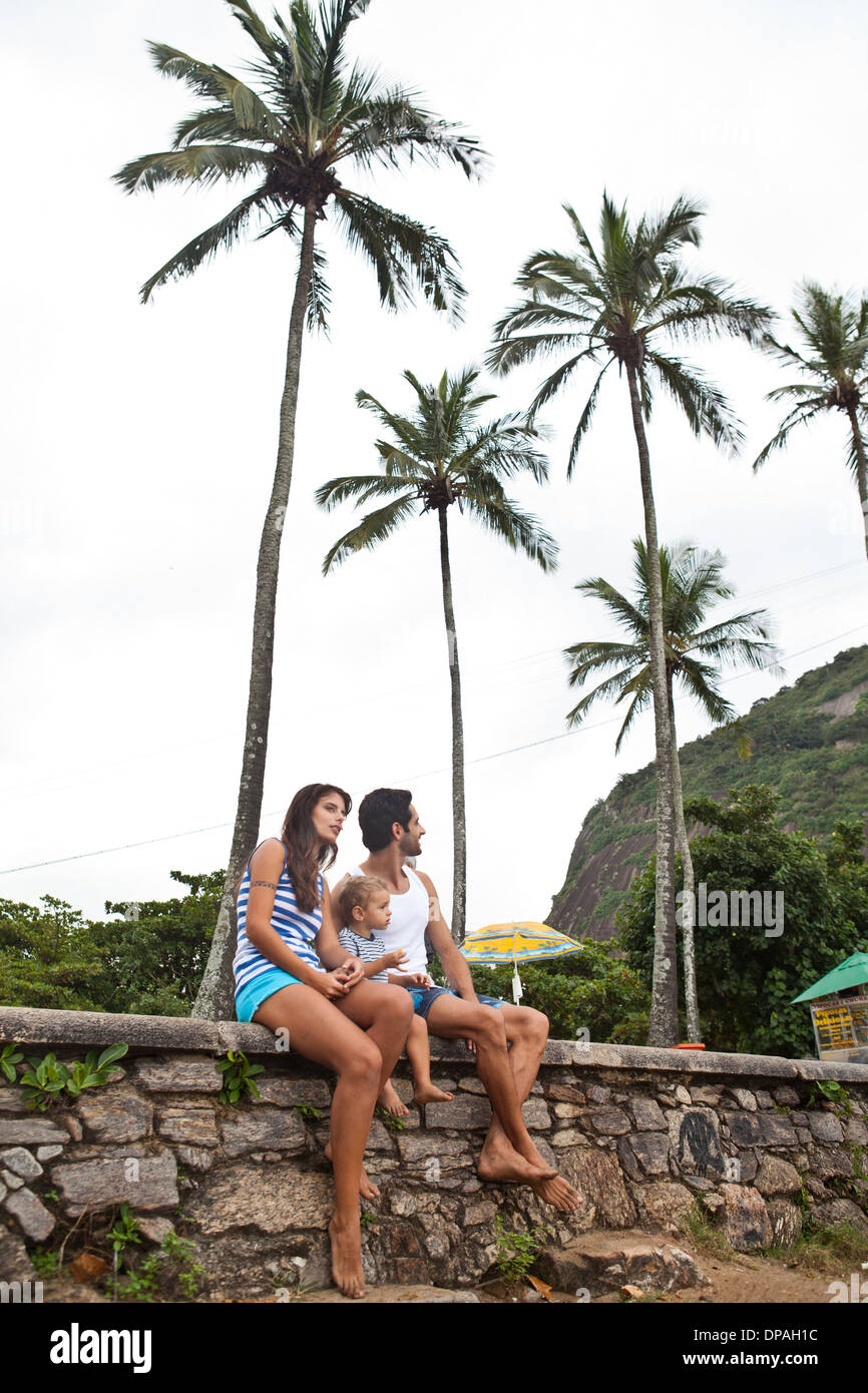 Family sitting on wall with palm trees - Stock Image