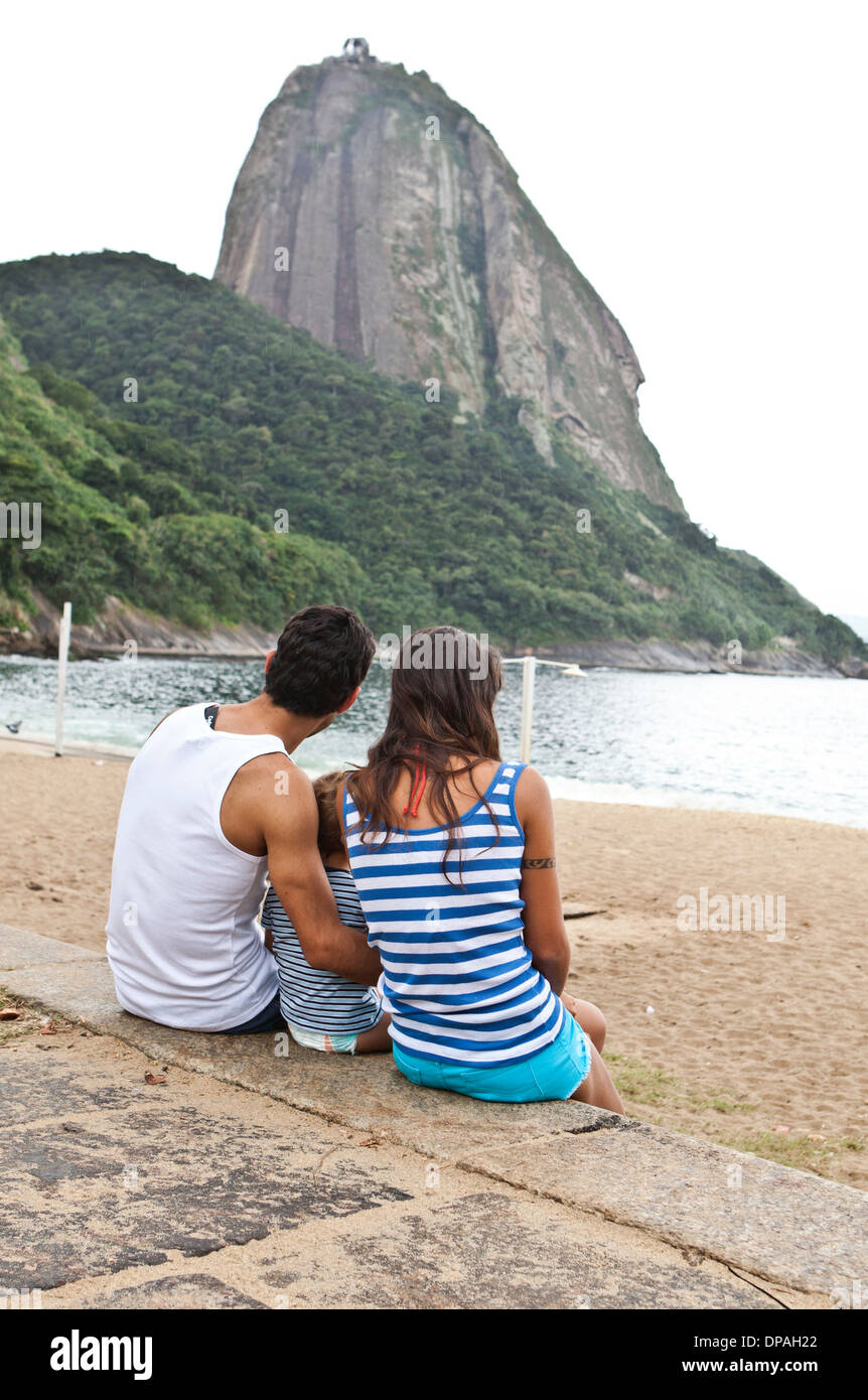 Family sitting on wall looking at Sugarloaf Mountain, Rio de Janeiro, Brazil - Stock Image