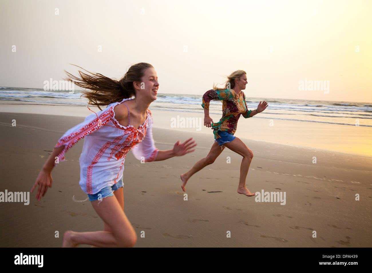 Mother and daughter running on beach - Stock Image