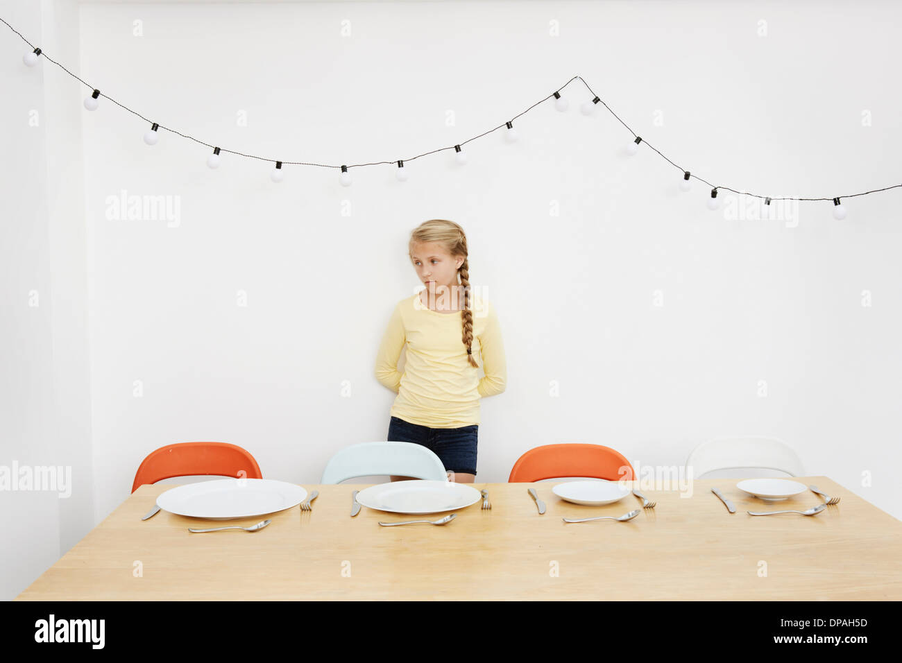 Girl waiting by table with empty plates - Stock Image