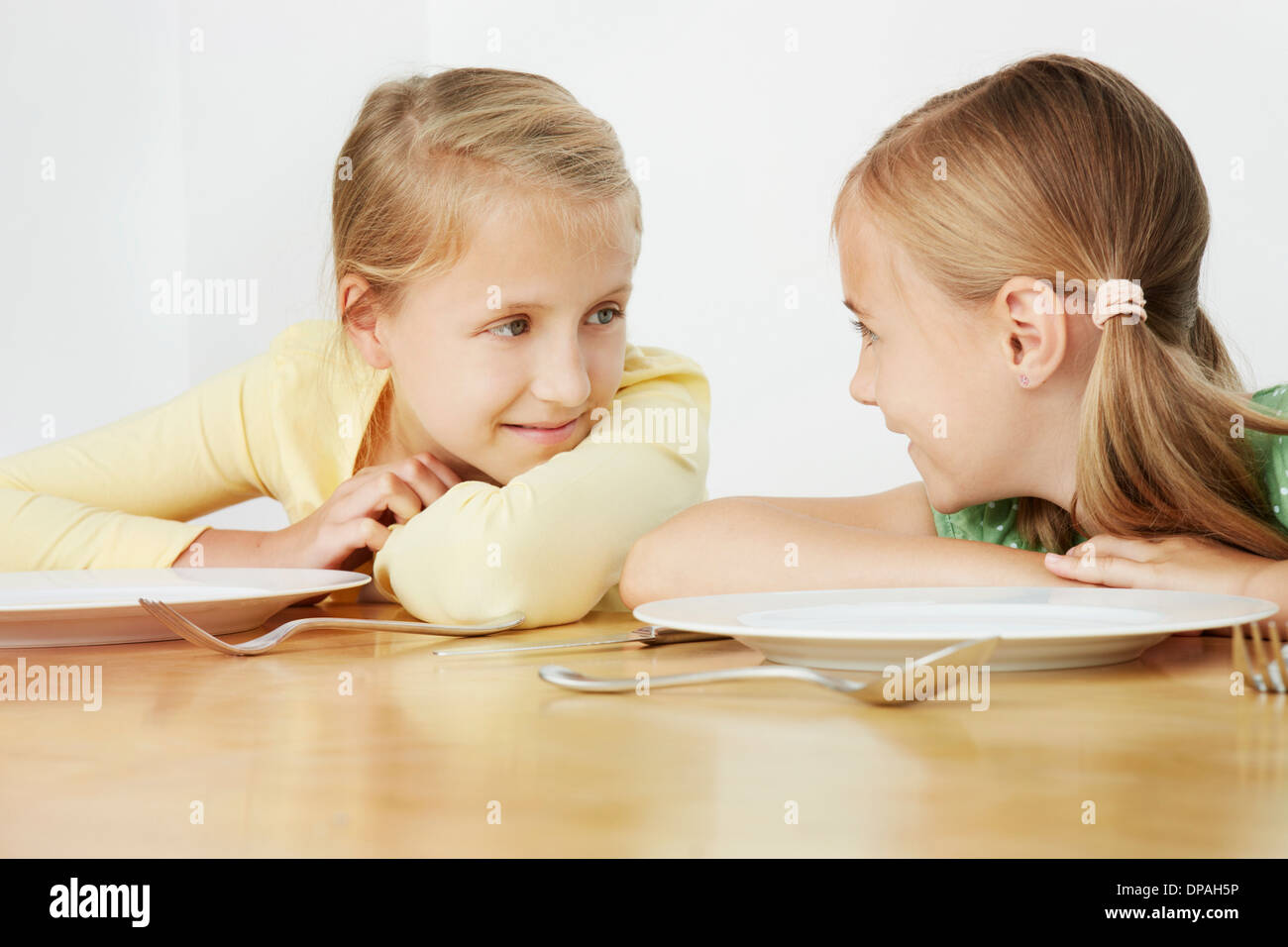 Two girls leaning on table with empty plates - Stock Image