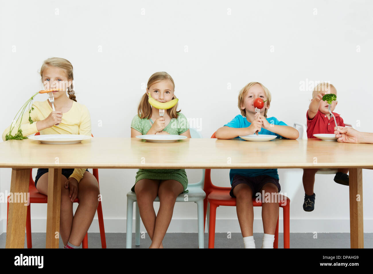Four children sitting at table with vegetables on forks - Stock Image