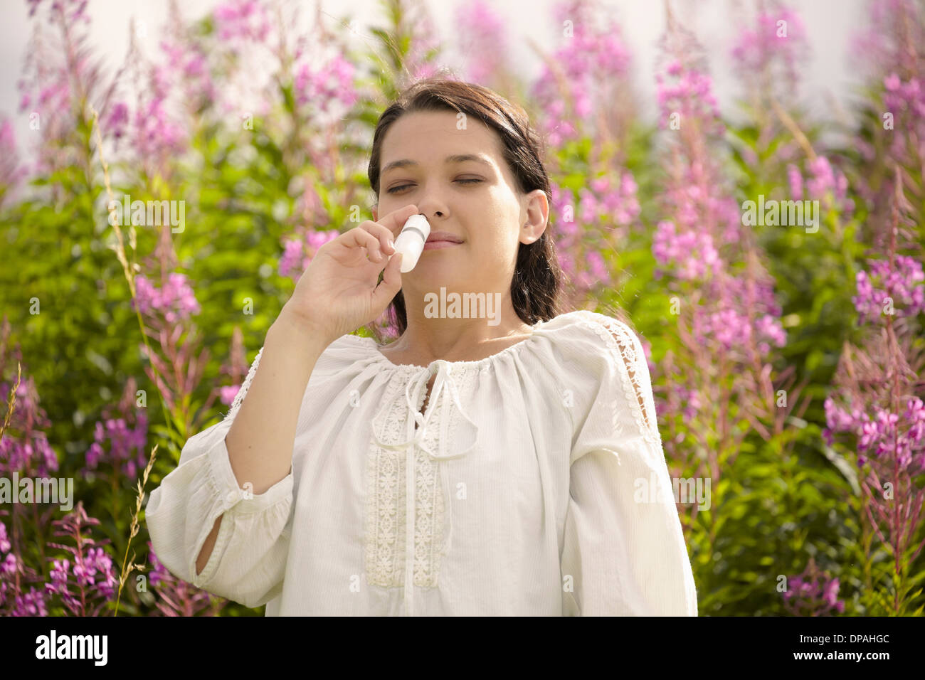 Woman using allergy relief nasal spray - Stock Image