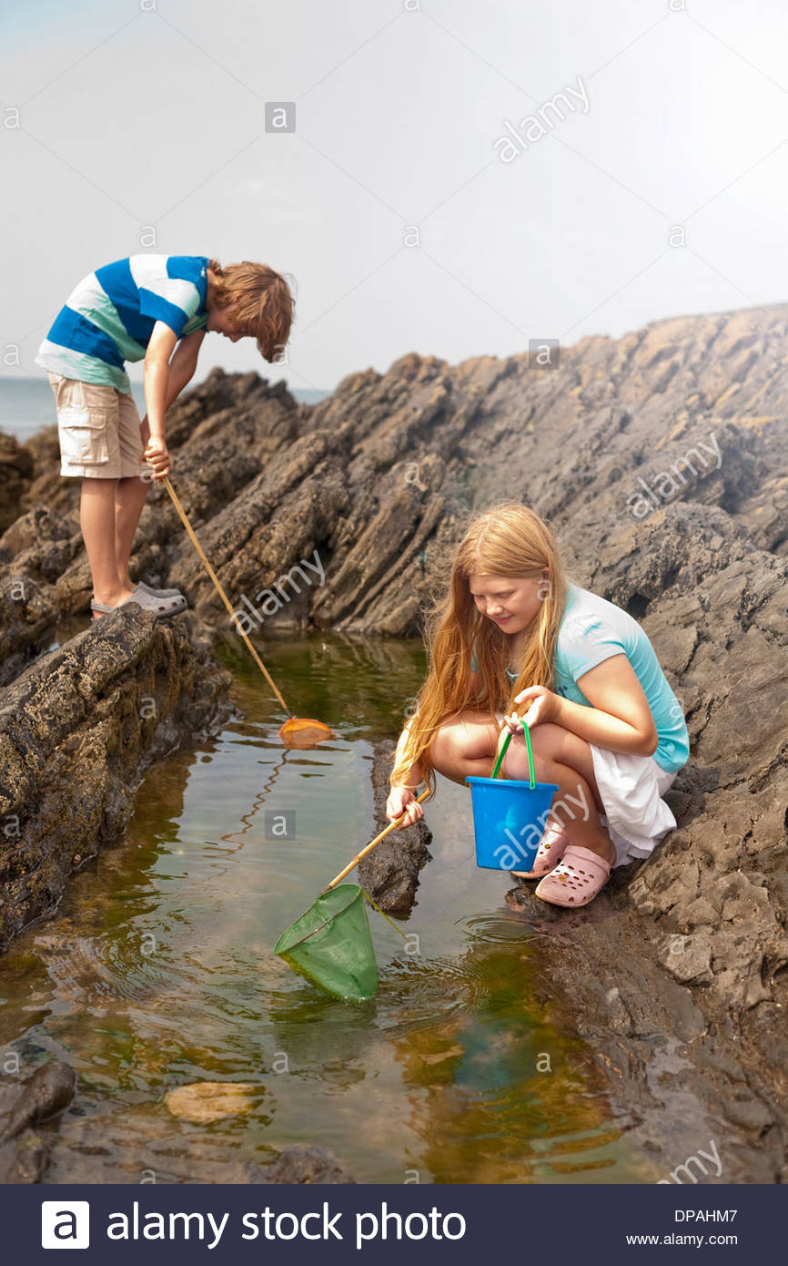 Two teenagers rock pooling - Stock Image