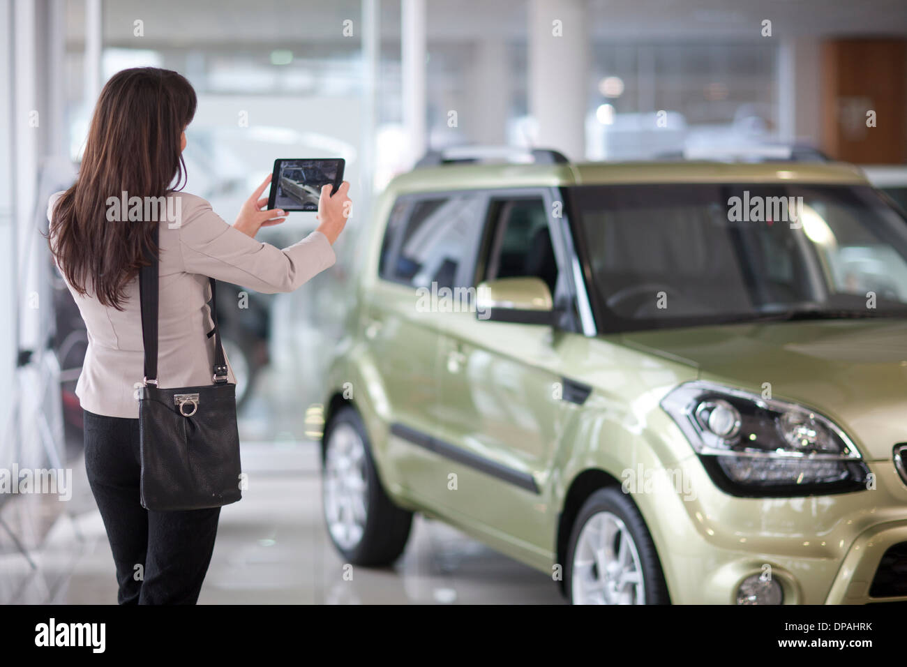 Mid adult woman taking photograph of car in showroom - Stock Image