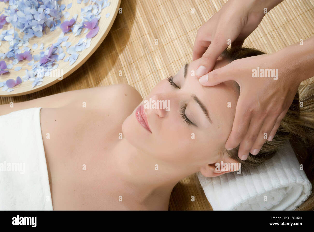 Woman at spa having forehead massaged Stock Photo