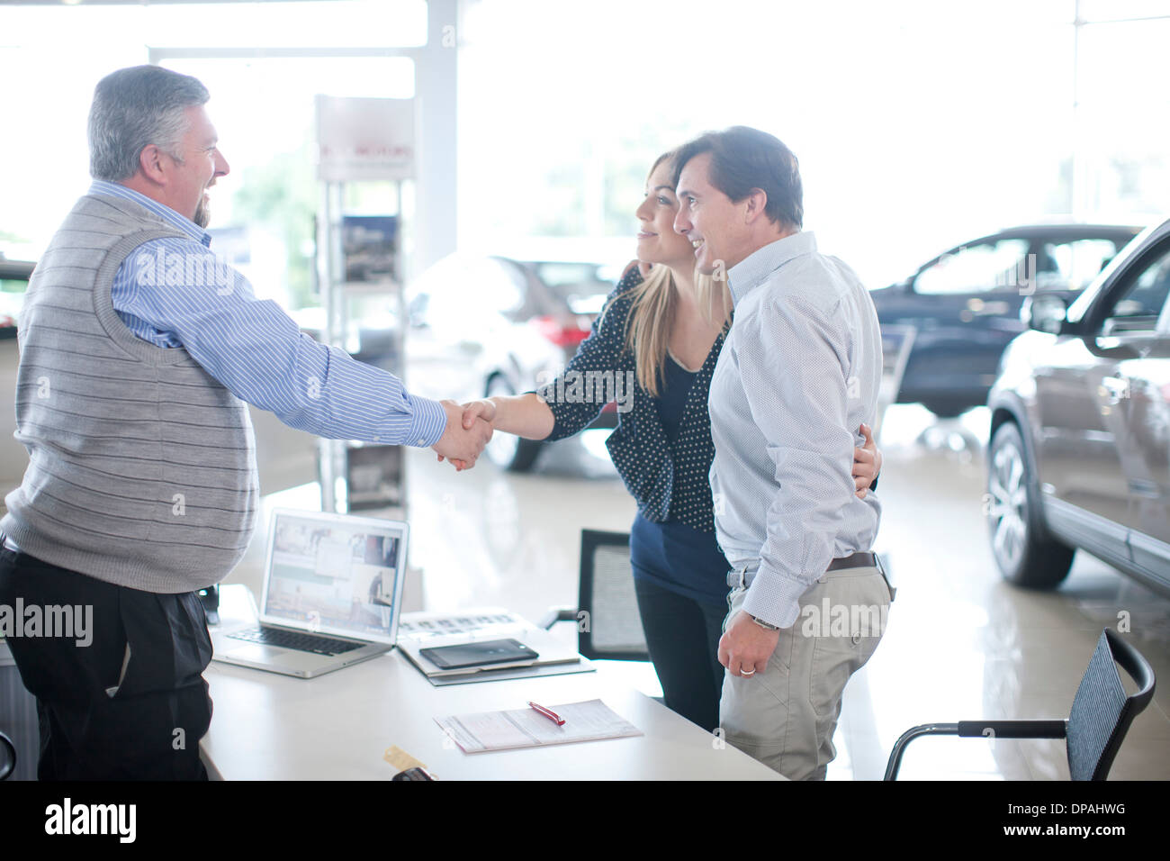 Car salesman and couple shaking hands in car showroom - Stock Image
