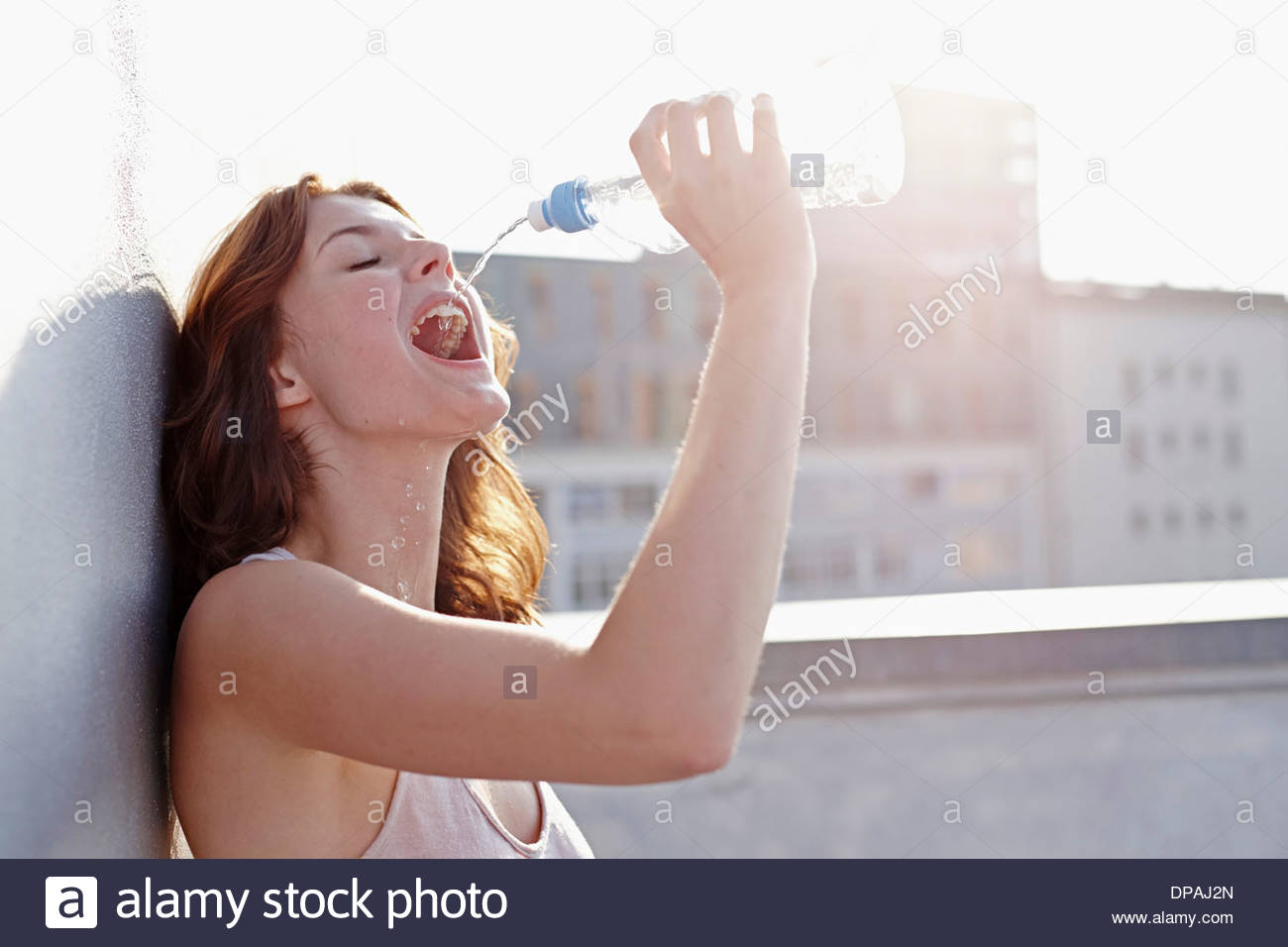 Portrait of young woman drinking mineral water - Stock Image