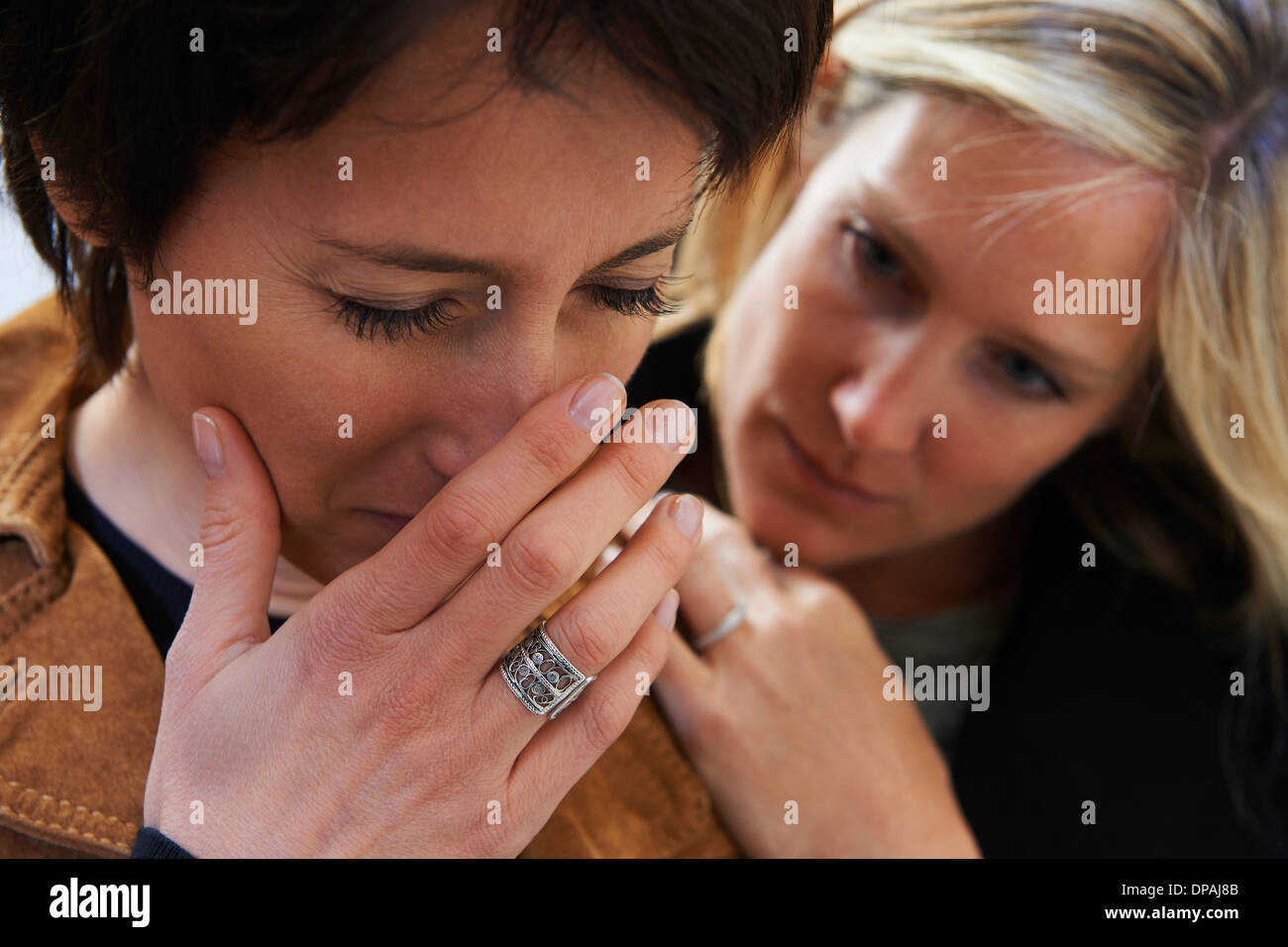 Close up of anxious woman with supportive friend - Stock Image
