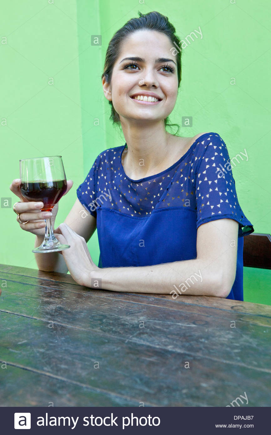Young woman at table outside cafe with wine - Stock Image